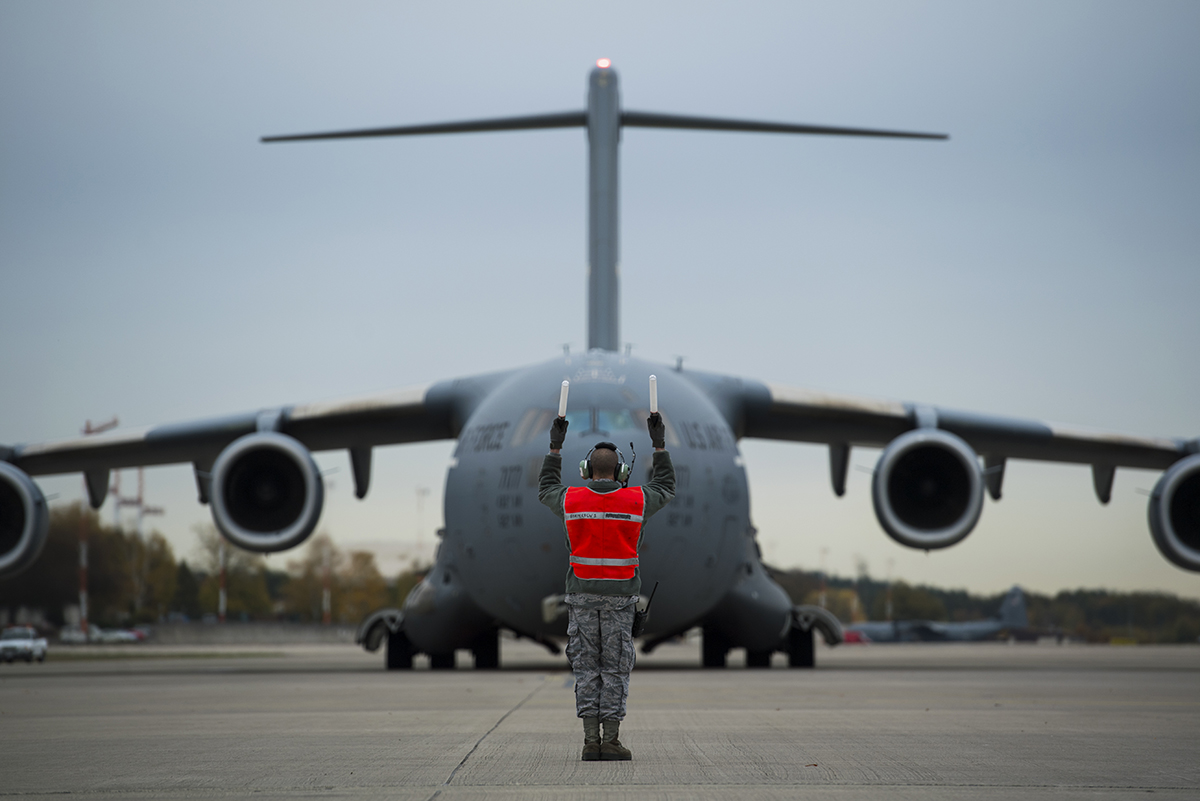 A crew chief marshals an Air Force C-17 Globemaster III on Ramstein Air Base, Germany Oct. 31, 2018. (Senior Airman Devin M. Rumbaugh/Air Force)