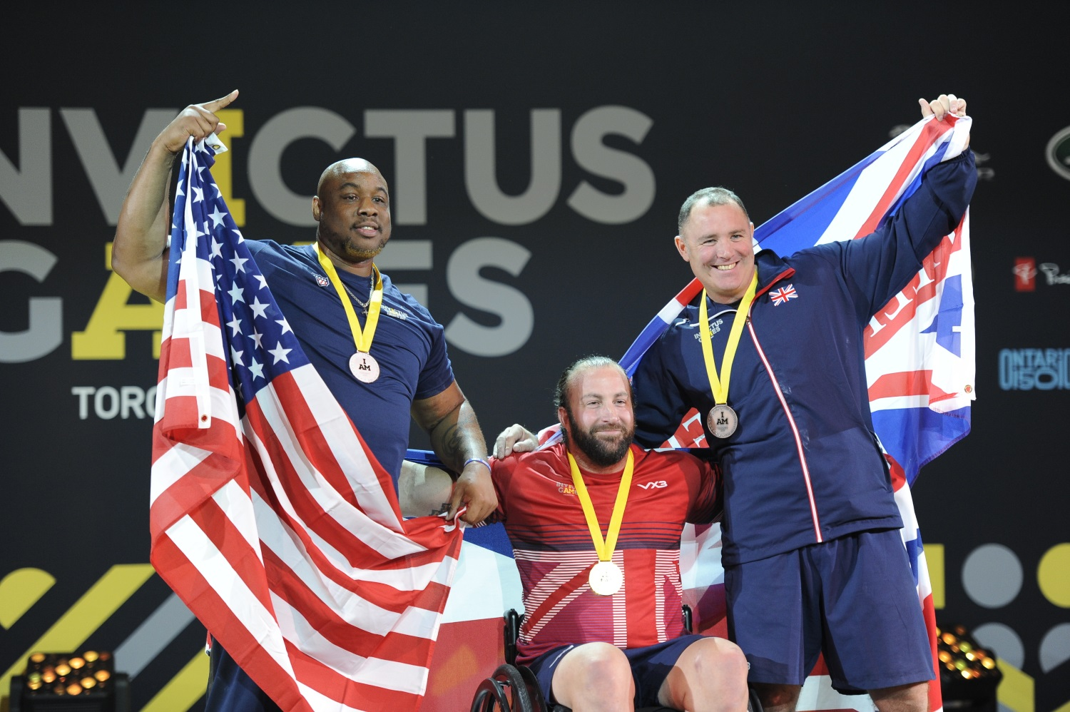The three men's powerlifting competition finalists pose for a photo after a medal ceremony during the 2017 Invictus Games at the Mattamy Athletics Centre in Toronto, Canada, on Sept. 26, 2017. Retired U.S. Air Force Staff Sgt. Nathaniel Bias, left, won silver. The Invictus Games are the sole international adaptive sporting event for injured active-duty and veteran service members. (Staff Sgt. Jannelle McRae/Air Force)