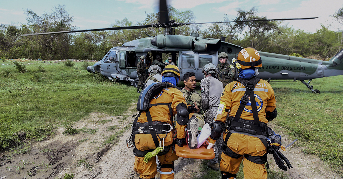 A Colombian rescue crew evacuates a victim in a Brazilian Air Force helicopter as part of an earthquake simulation exercise held by Air Force troops from Colombia, the Dominican Republic, Peru, Brazil and the United States at the Palenquero Air Force base in Puerto Salgar, Cundinamarca Department, Colombia, on September 6, 2018. - Air Force crews from 12 countries took part in the