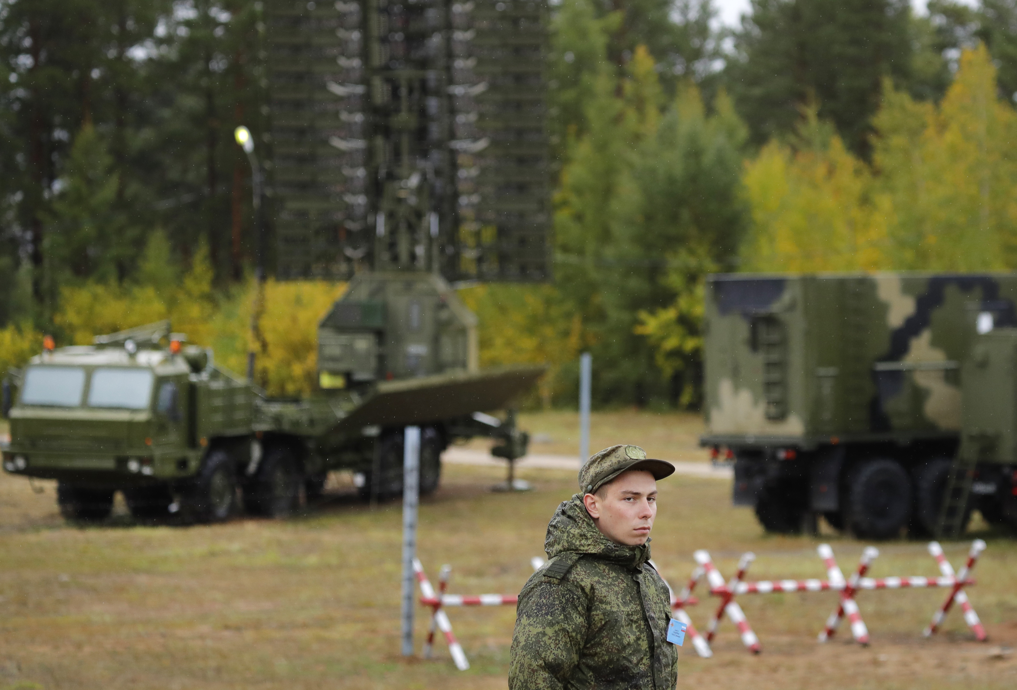 A Russian soldier stands in front of a Nebo-M radar deployed in a forest, during a military exercises on training ground