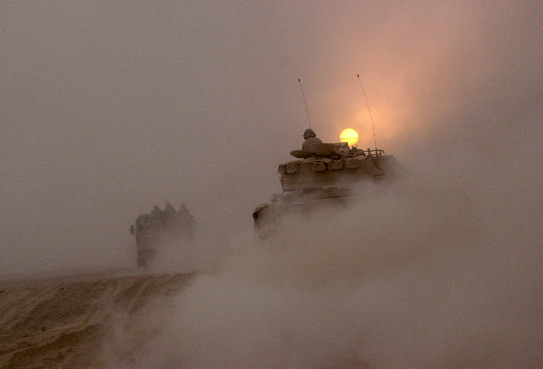 Vehicles from the U.S. Army's 3rd Infantry Division rumble down a road north into Iraq. The Convoy has been moving for two days now on their drive north to take down the Iraqi regime. Up until this point the convoy has received little enemy contact. (Warren Zinn/Army Times)