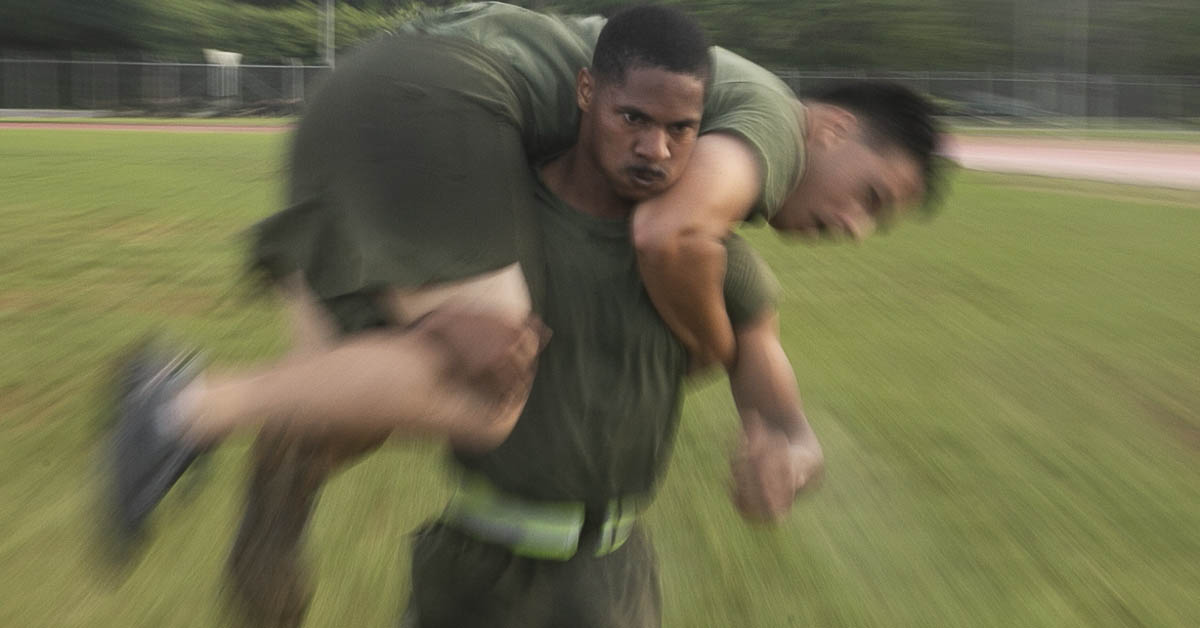 Sgt. Wesley Davison, a field radio operator with the 31st Marine Expeditionary Unit, fireman carries a fellow NCO during a Force Fitness Instructor led High Intensity Tactical Training session at Camp Hansen, Okinawa, Japan. (Gunnery Sgt. T. T. Parish/Marine Corps)