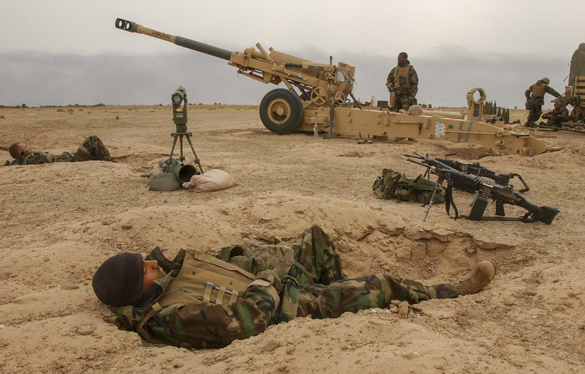 03/22/2003 Images shot in southern Iraq Photo by Jud McCrehin/Marine Corps Times Lance Cpl. Guilbert Alce, 23, with battery M, 3rd Battalion, 11th Marine Regiment takes a nap in his sleeping hole near the 155mm Howitzer he works as a powder man on in an artillery position in southern Iraq.