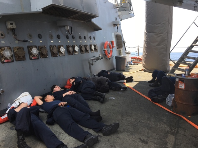 Sailors aboard the warship Fitzgerald rest as the ship makes its way back to land following a June 2017 collision that killed seven of their shipmates. (Photo provided to Navy Times)
