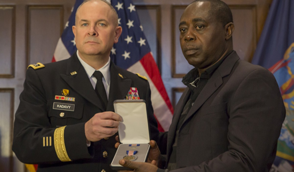 Lt. Gen. Timothy Kadavy, director of the Army National Guard, presents Kwabena Mensah, father of Pfc. Emmanuel Mensah, with the Soldiers Medal, the Army's top award for valor outside of combat during a ceremony on Feb. 16, at Fordham University in the Bronx, New York. (Sgt. Harley Jelis/Army)