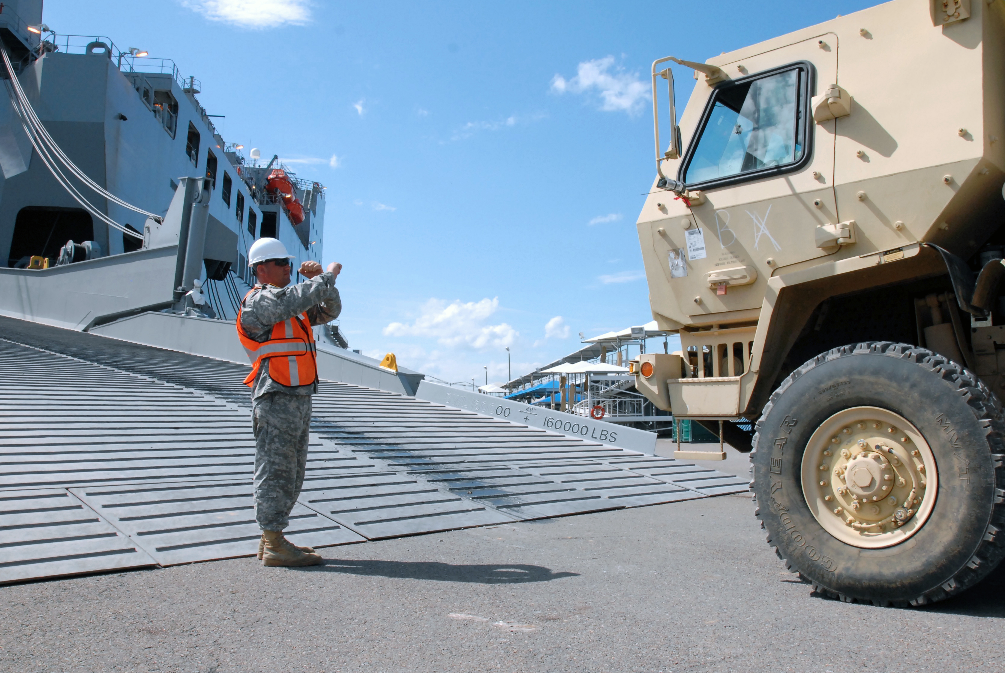 U.S. Army Staff Sgt. Craig Woolley guides one of the last pieces of equipment to be loaded onto the Navy's Military Sealift Command ship, the USNS Benavidez. (John Orrell/U.S. Army)