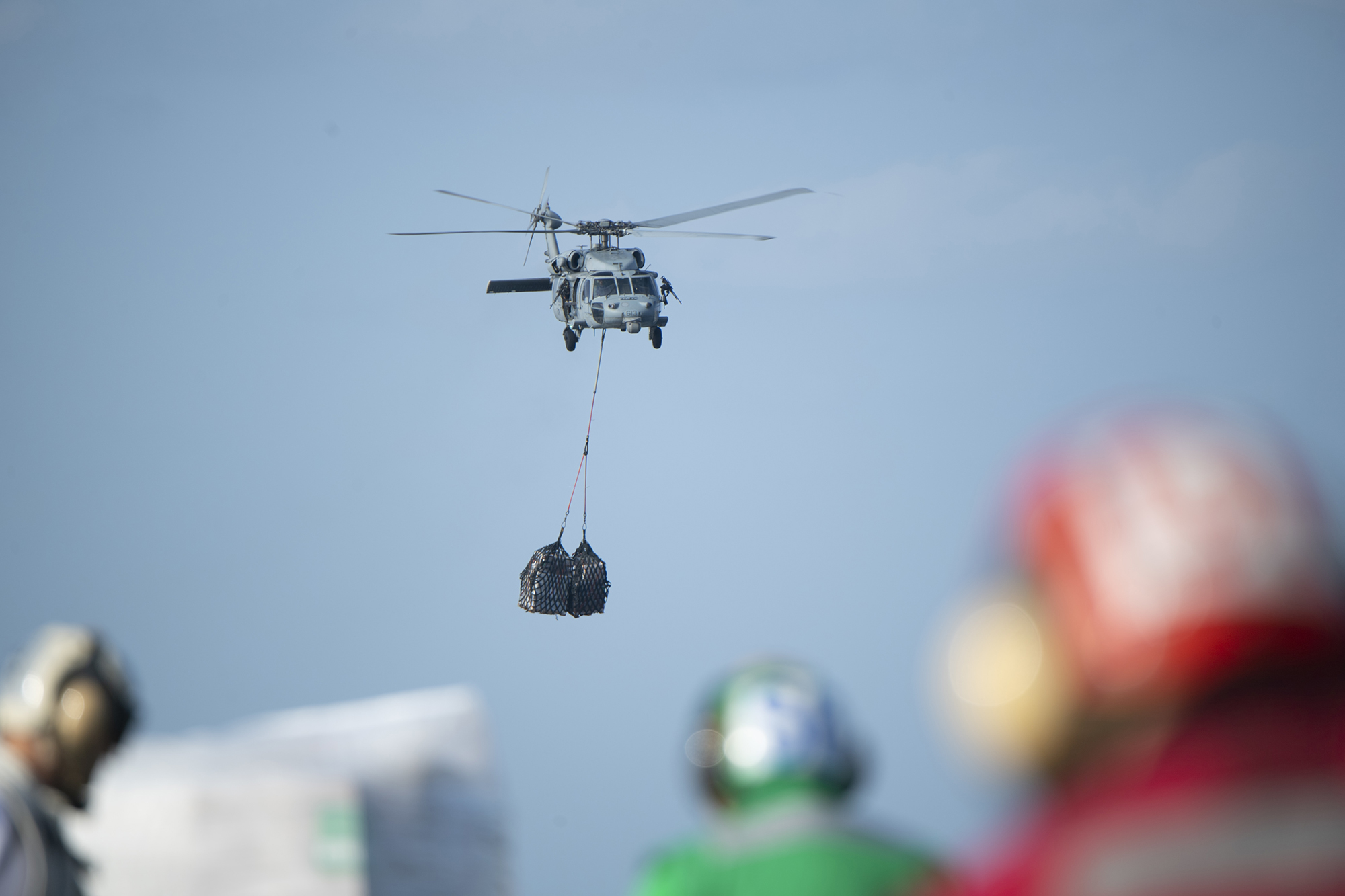 An MH-60S Sea Hawk helicopter transports cargo to the aircraft carrier USS Harry S. Truman (CVN 75) from the USNS Wally Schirra (T-AKE 8) during a replenishment-at-sea in the Arabian Sea on Dec. 21, 2019. (Mass Communication Specialist 2nd Class Jake Carrillo/Navy)