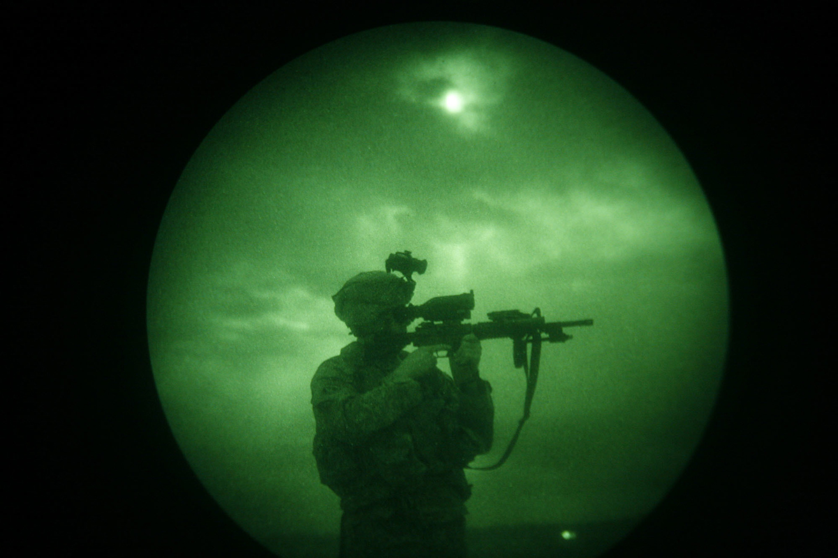 In this April 21, 2008, file photo, a U.S soldier looks through the scope of his weapon during a night patrol in Mandozai, in Khost province, Afghanistan, seen through night vision equipment. About 400,000 veterans had a PTSD diagnosis in 2013, according to the Veterans Affairs health system. (Rafiq Maqbool/AP)