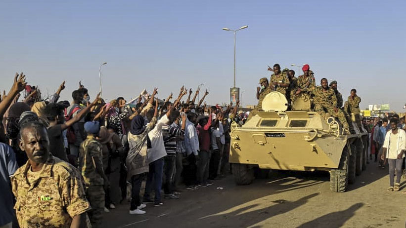 Sudanese protesters flash the victory sign at a passing military vehicle as they rally for a second day outside the military headquarters in the capital Khartoum on April 7, 2019. - Sudanese police fired tear gas at thousands of protesters who rallied outside the army headquarters for a second day urging the military to back them in demanding President Omar al-Bashir resign. (AFP/Getty Images)