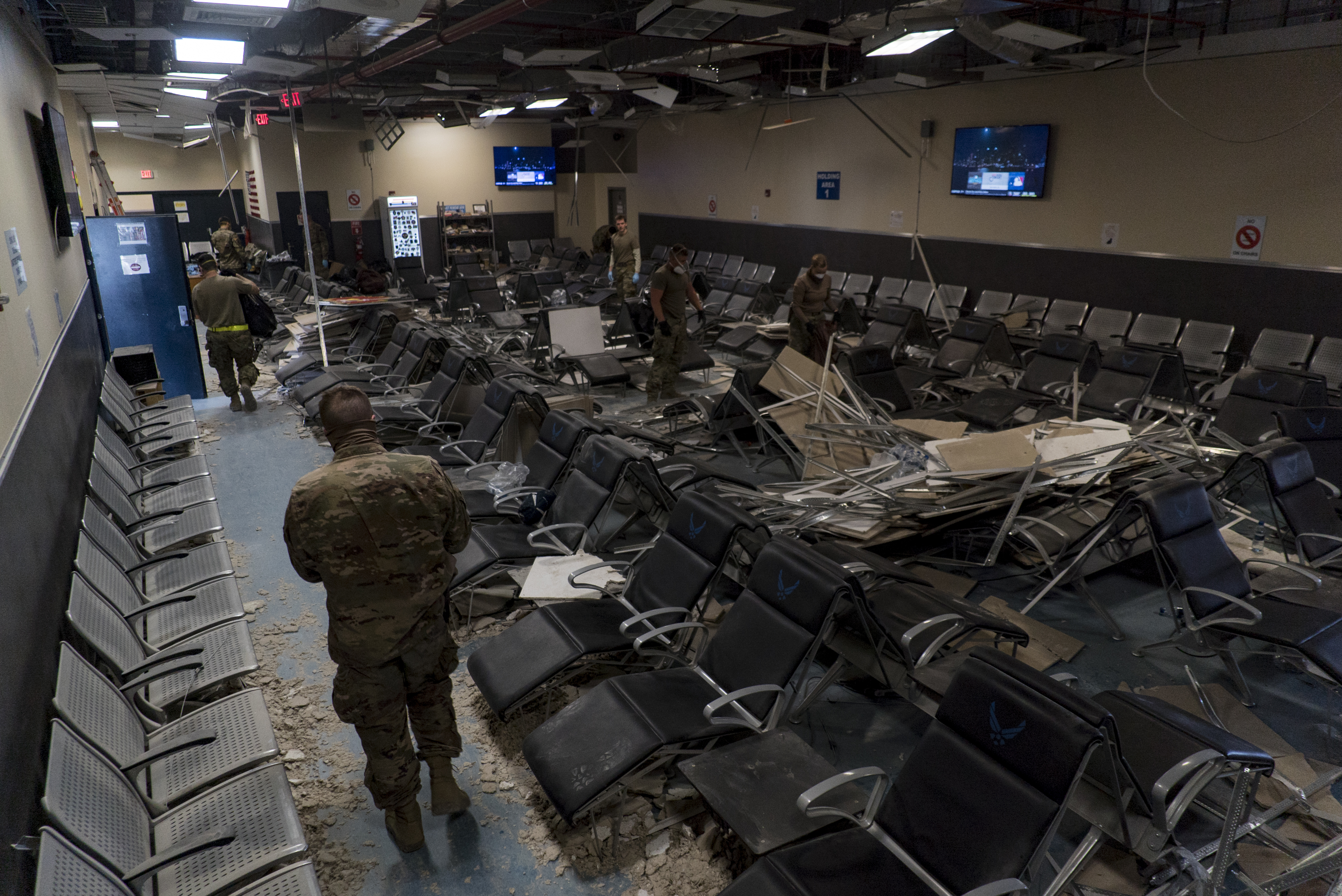 U.S. Air Force airmen work together to clear debris inside the passenger terminal the day after a Taliban-led attack at Bagram Airfield, Afghanistan, Dec. 12, 2019. (Airman 1st Class Brandon Cribelar/Air Force)