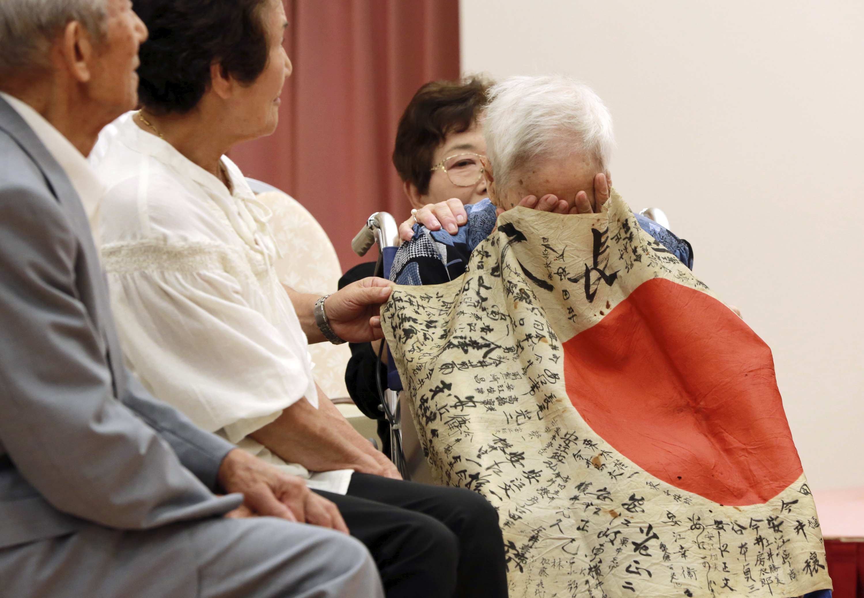 Sayoko Furuta, right, 93, reacts as she is covered with a Japanese flag with autographed messages which was owned by her brother Sadao Yasue, who was killed in the Pacific during World Work II, during a ceremony in Higashishirakawa, in central Japan's Gifu prefecture Tuesday, Aug. 15, 2017. (Eugene Hoshiko/AP)