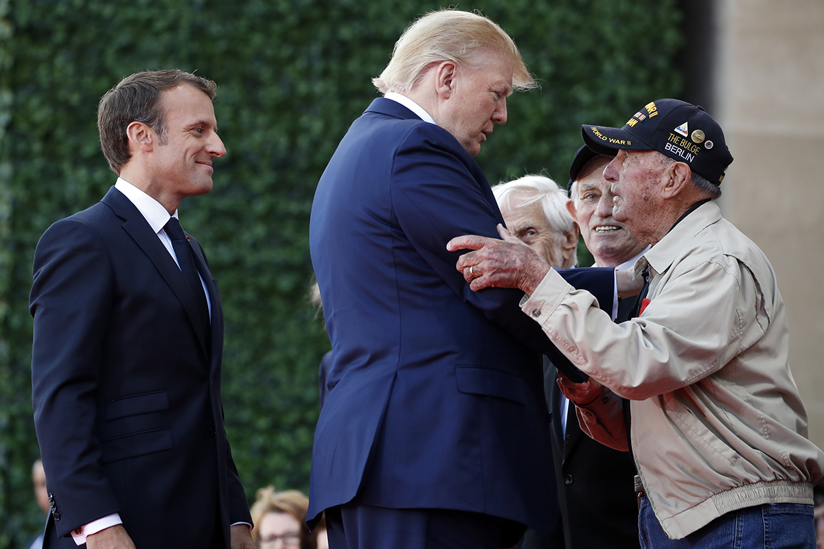 President Donald Trump and French President Emmanuel Macron, talk to a World War II veteran during a ceremony to commemorate the 75th anniversary of D-Day at the American Normandy cemetery, Thursday, June 6, 2019, in Colleville-sur-Mer, Normandy, France. (Alex Brandon/AP)