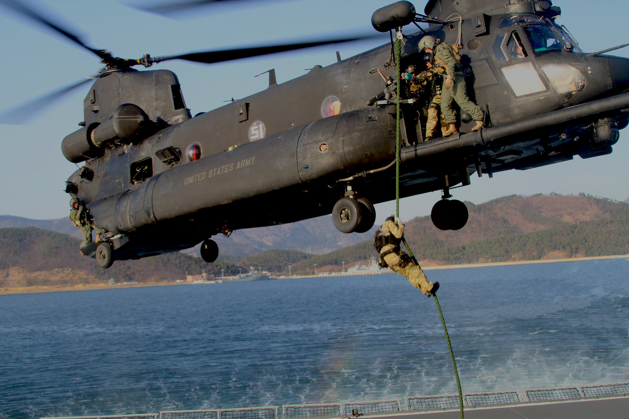 A U.S. Navy SEAL with Naval Special Warfare Group 1 fast ropes from an Army MH-47 Chinook helicopter onto the aft deck of the fast combat support ship ROKS Hwacheon (AOE 59) March 20, 2012, in Jinhae Harbor, South Korea, during Foal Eagle 2012. (Sgt. Aaron Rognstad/Army)