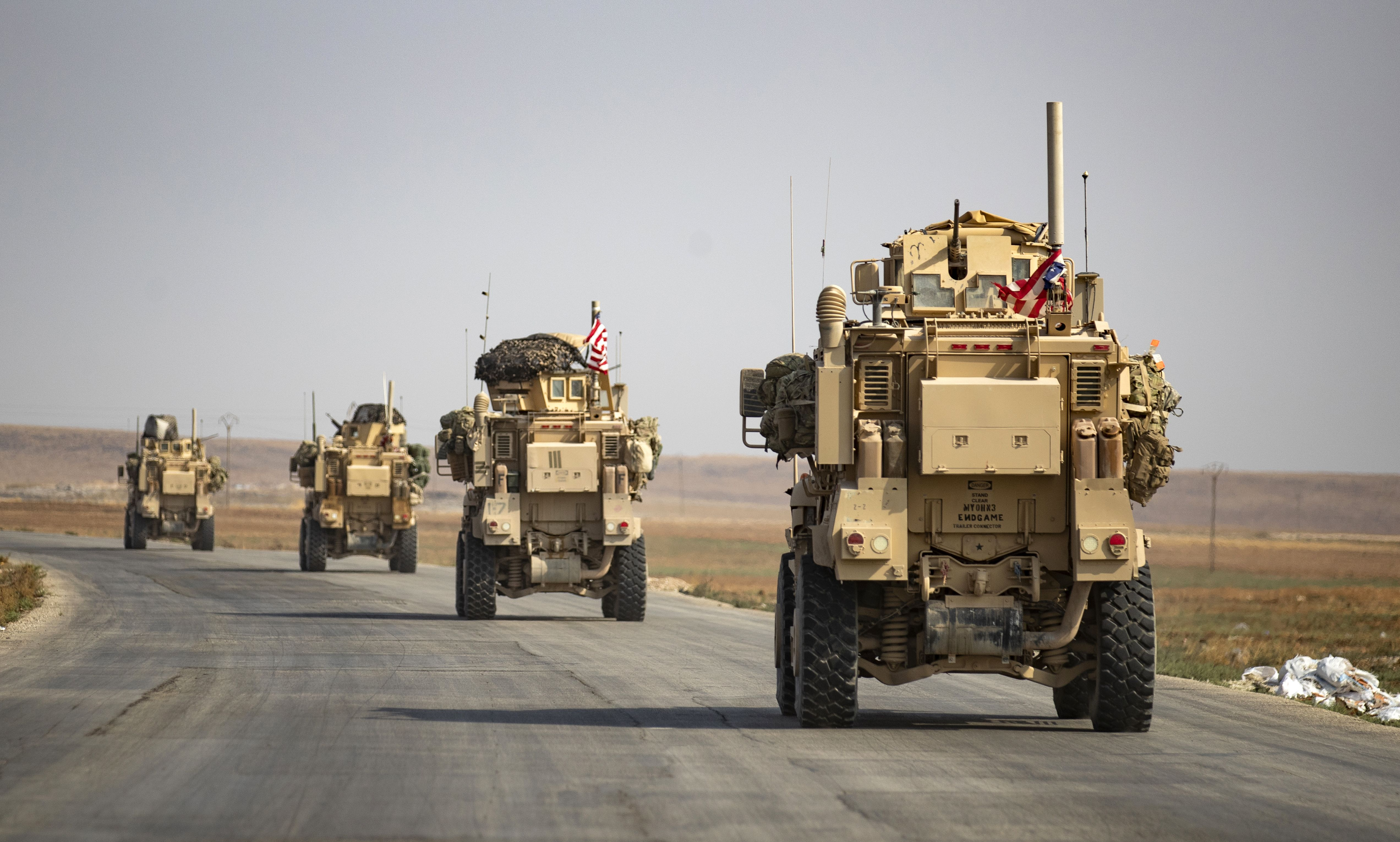 U.S. military vehicles drive on a road after US forces pulled out of their base in the Northern Syrian town of Tal Tamr, on Oct. 20, 2019. (Delil Souleiman/AFP via Getty Images)