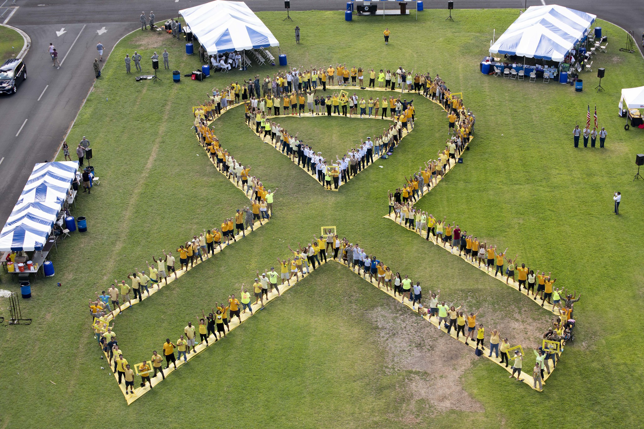 Hawaii-based service members from every branch of service, Department of Defense personnel, and military and DoD families form a human chain in the shape of a yellow suicide awareness ribbon on Sept. 5, 2018, in support of National Suicide Awareness Month at Joint Base Pearl Harbor-Hickam. (Mass Communication Specialist 1st Class Corwin Colbert/Navy)
