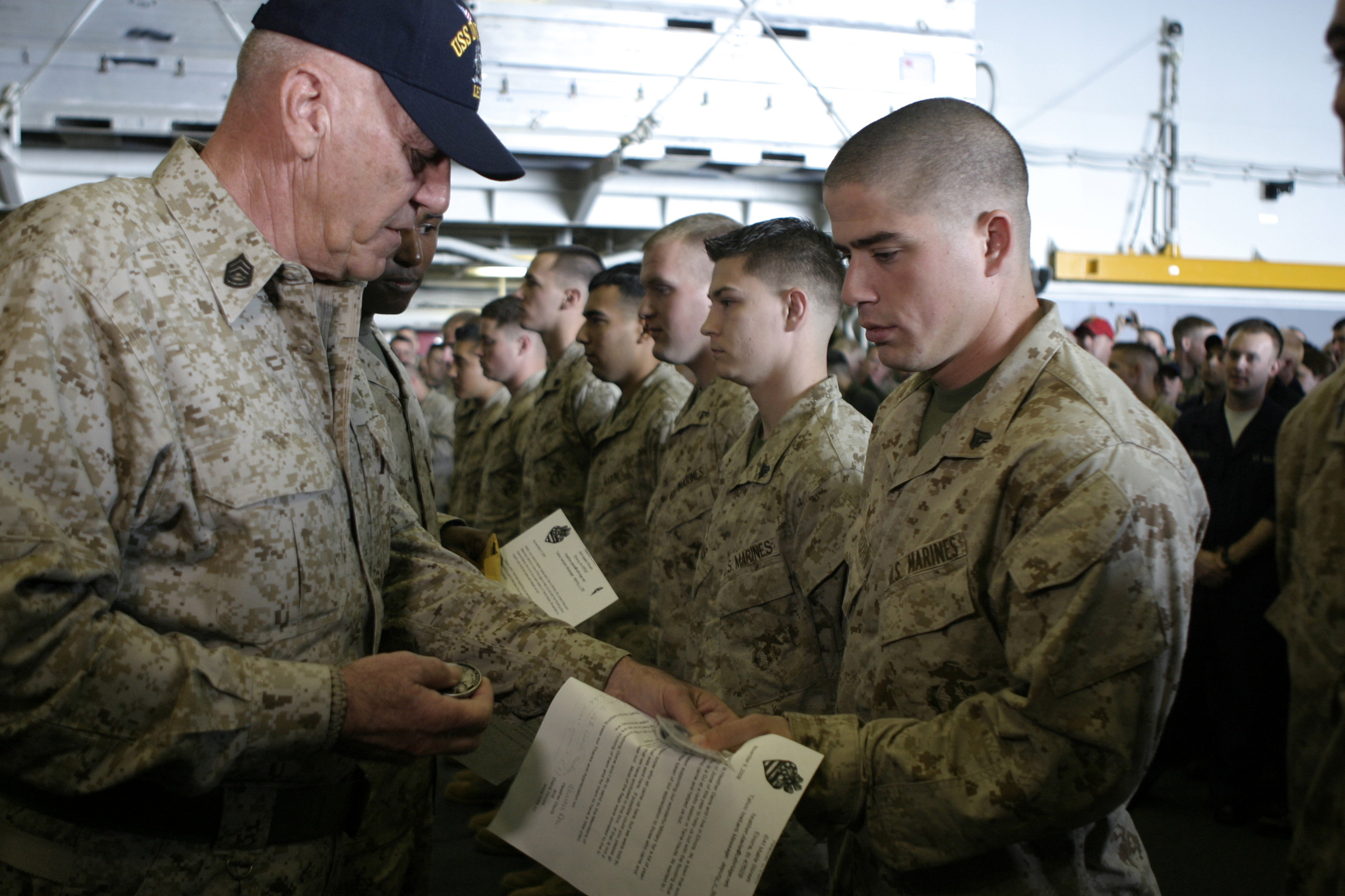 Actor and Marine Corps icon Gunnery Sgt. R. Lee Ermey hands Cpl. Trevor J. Blackburn, assigned to Battalion Landing Team 2/6, 26th Marine Expeditionary Unit, a small American flag aboard the amphibious assault ship USS Iwo Jima. The flag was sent from residents of Elnora, Ind., as a token of thanks after the Marines and Sailors from the 26th MEU helped reinforce the town's levees during a flood earlier this year. Ermey visited the USS Iwo Jima as a Moral, Welfare and Recreation event for deployed troops during the holiday season. (Cpl. Patrick M. Johnson-Campbell/Marine)