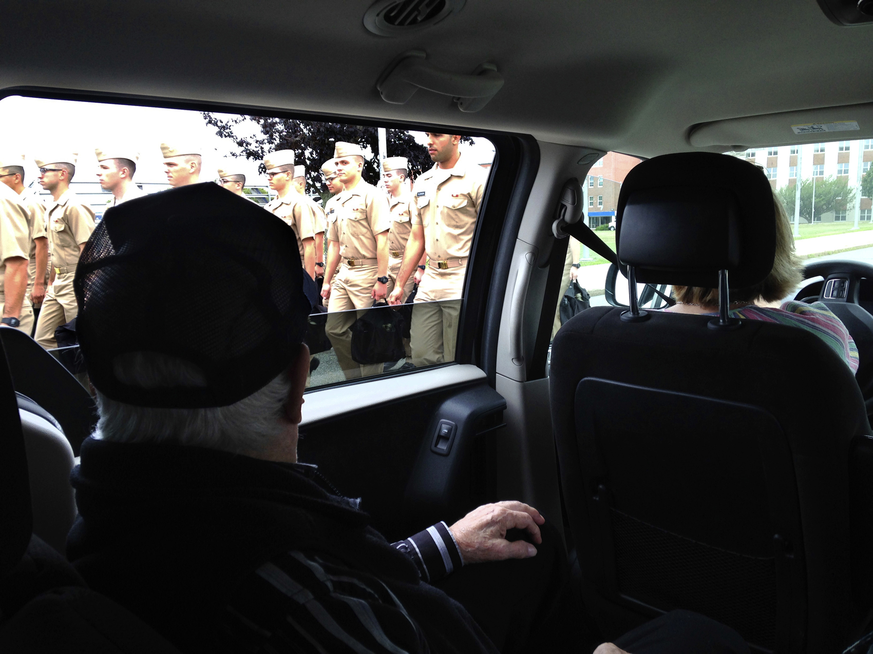 WWII veteran Edmund DelBarone looks out the window of a van while passing an officer candidate class during a tour at Naval Station Newport, in Newport, R.I., Thursday July 27, 2017. DelBarone, a 96-year-old World War II veteran, once dreamed of returning to a Navy installation to reminisce about his naval career, and help of a nonprofit it has become a reality. (Jennifer McDermott/AP)