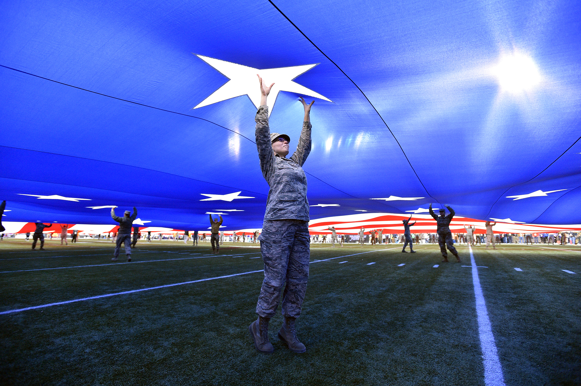 A member of the U.S. Air Force holds up a full-field American flag as it is displayed on the field before the Mitsubishi Motors Las Vegas Bowl between the Washington Huskies and the Boise State Broncos at Sam Boyd Stadium on Dec. 21, 2019 in Las Vegas. (David Becker/Getty Images)