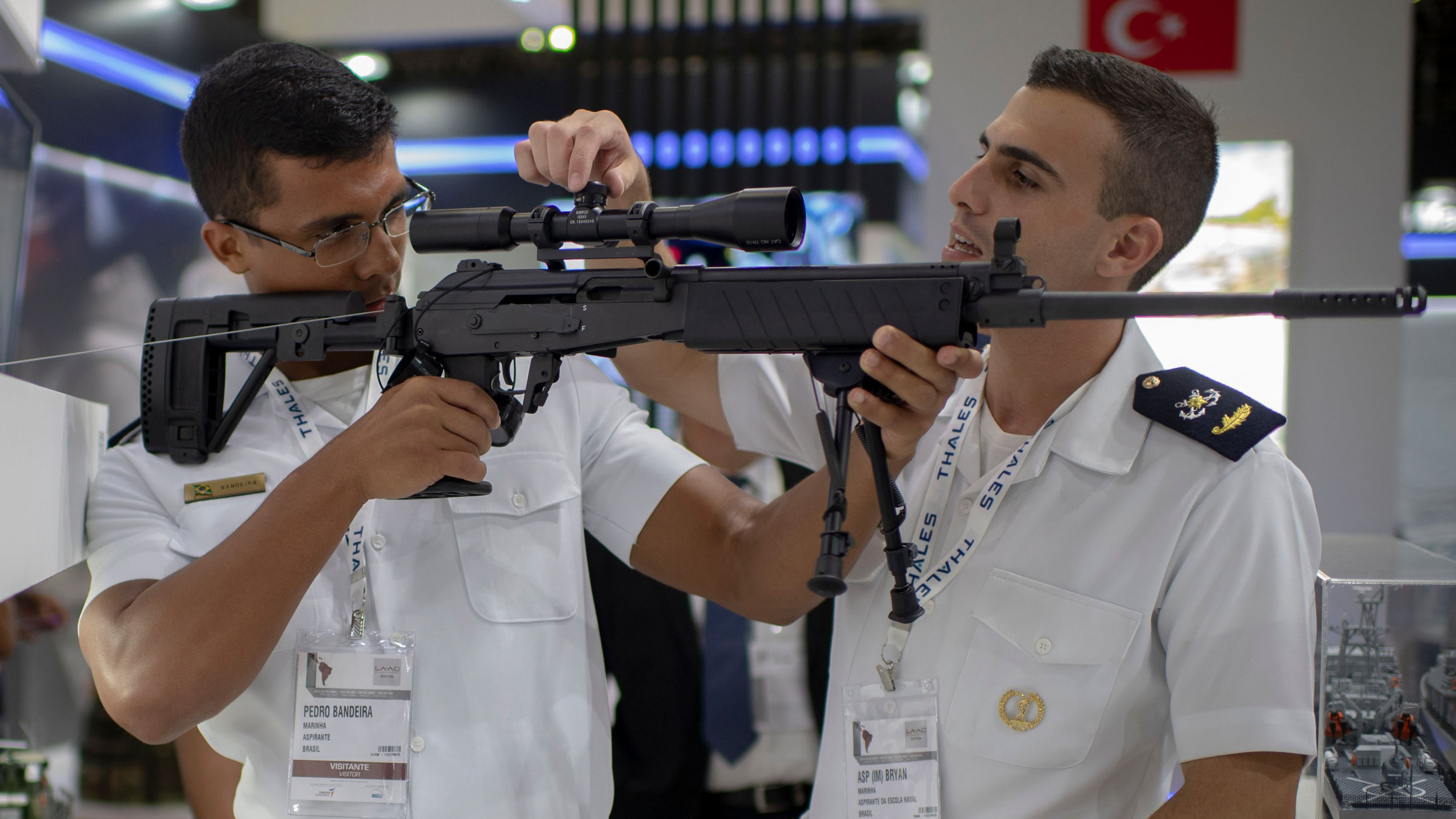 Brazilian navy members inspect the riflescope of a firearm during the Defense and Security International Fair 2019 (LAAD 2019) at Riocentro Expo Center in Rio de Janeiro, Brazil, on April 02, 2019. (MAURO PIMENTEL/AFP/Getty Images)
