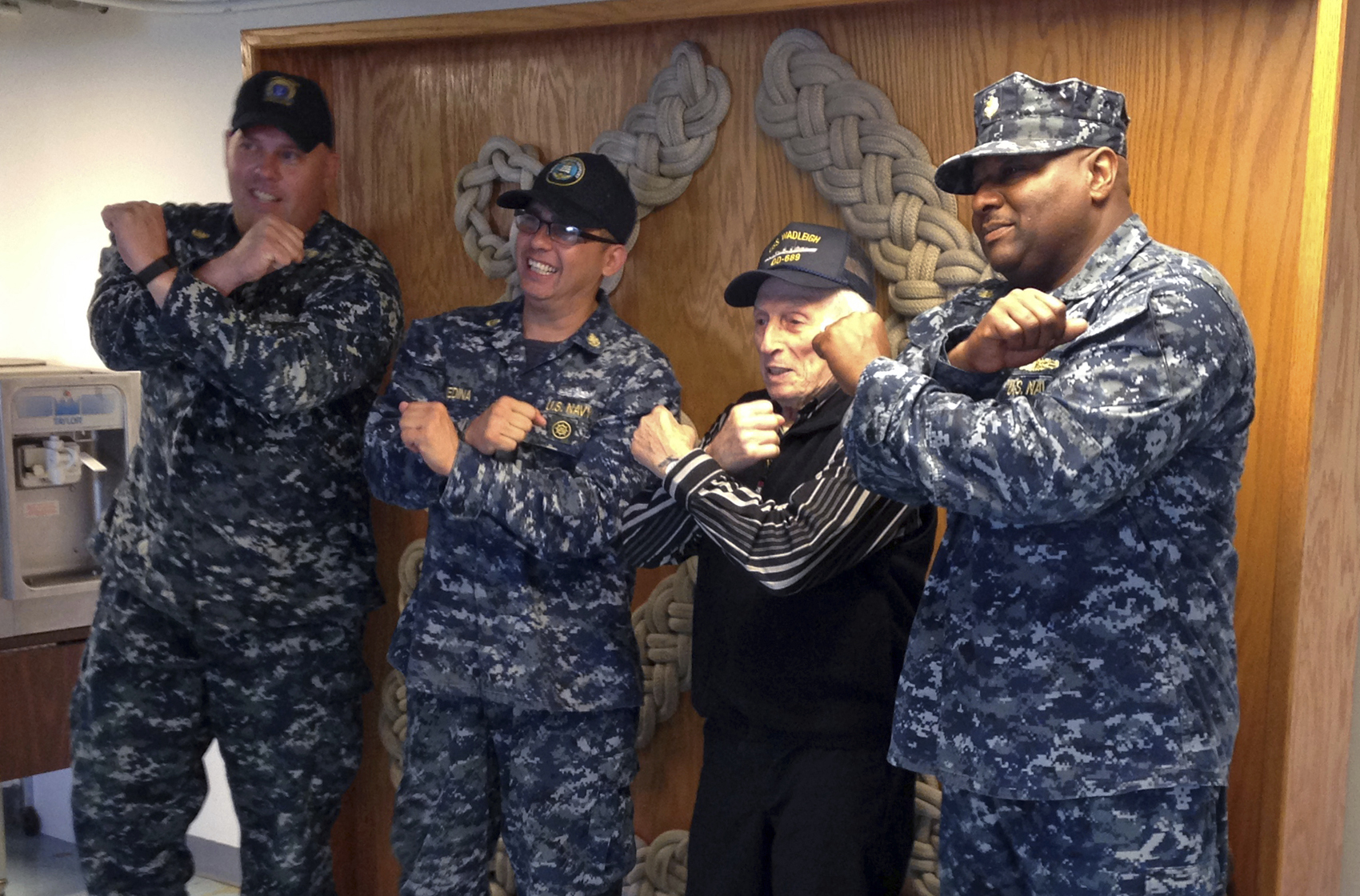 WWII veteran Edmund DelBarone, second from right, makes the U.S. Navy crossed anchors symbol with his arms while posing for a photograph at Naval Station Newport, in Newport, R.I., Thursday July 27, 2017. DelBarone, a 96-year-old World War II veteran, once dreamed of returning to a Navy installation to reminisce about his naval career, and help of a nonprofit it has become a reality. (Jennifer McDermott/AP)
