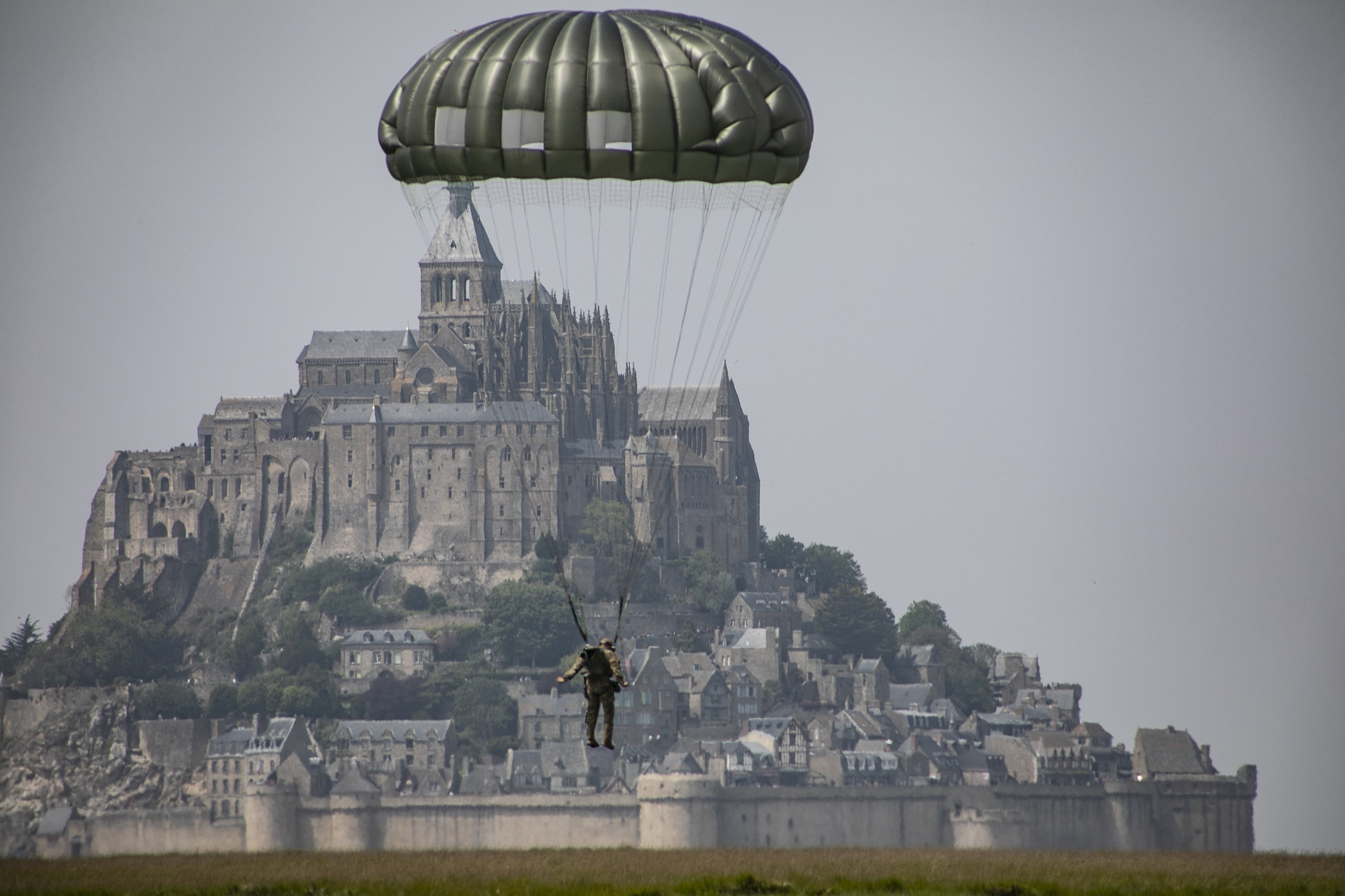 A paratrooper assigned to the U.S. Army's 10th Special Forces Group (Airborne) conducst an airborne operation near the island of Mont Saint Michel, Avranches, France, on May 18, 2019. This event comes at the invitation of the Mayor of Avranches in commemoration of World War ll special operations that laid the success for the Allied liberation of France, and a celebration of the strong Alliance between France and the United States. (Sgt. Alexis K. Washburn/Army)