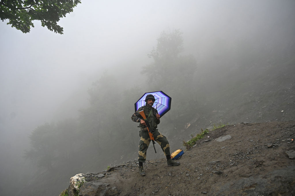 An Indian Border Security Force (BSF) soldier stands guard during heavy rainfall at the PishuTop, some 127 km southeast of Srinagar, on July 27, 2019 during the annual Hindu pilgrimage to the holy cave shrine of Amarnath. - (TAUSEEF MUSTAFA/AFP/Getty Images)