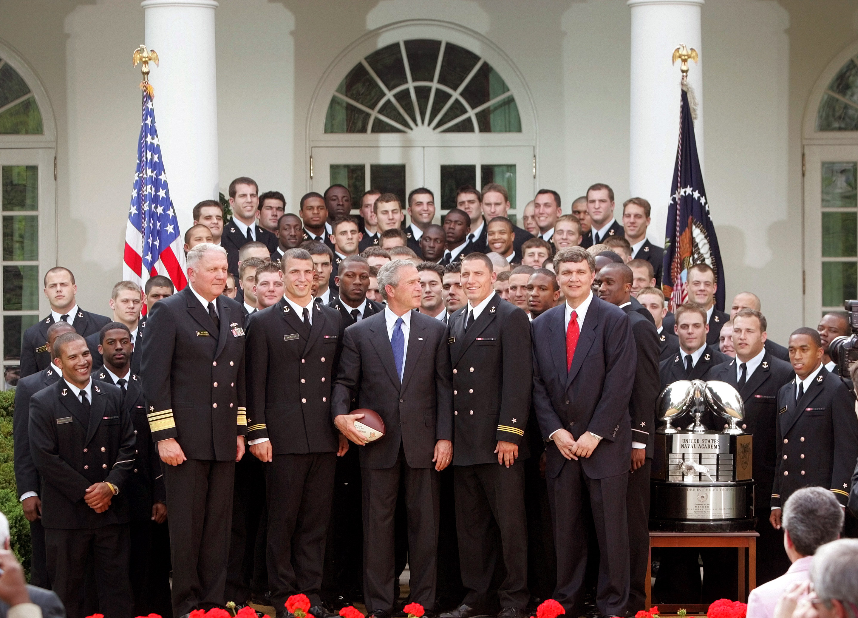President Bush, center, poses for a photograph with members of the U.S. Naval Academy football team after the presentation of the Commander-In-Chief's Trophy in Rose Garden at the White House Wednesday, April 20, 2005 in Washington. Bush hailed the Naval Academy football team for winning the commander-in-chief's trophy, the first time since 1981. The trophy goes each year to the team with the best record in games among the three service academies. (AP Photo/Pablo Martinez Monsivais)