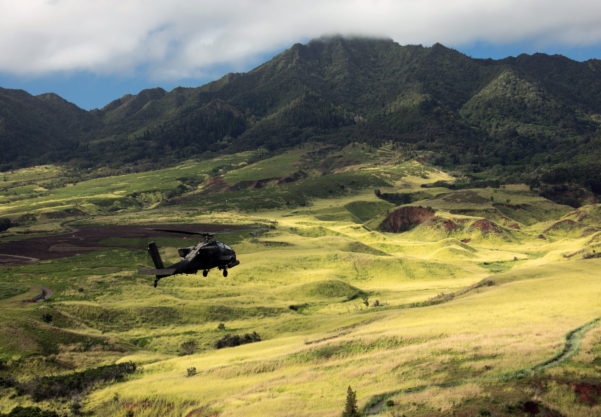 An Army AH-64D Apache helicopter flies in formation for the 25th Infantry Division Review over Schofield Barracks, Hawaii, Dec. 21, 2018. (Staff Sgt. Ian Morales/Army)