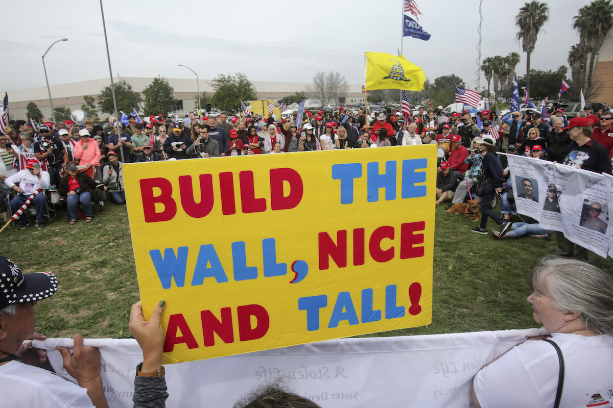 Supporters of President Donald Trump display signs during a rally attended by about 500 people in San Diego, Calif., on March 13, 2018, where he was visiting the nearby border wall protoypes. (Bill Wechter/AFP via Getty Images)
