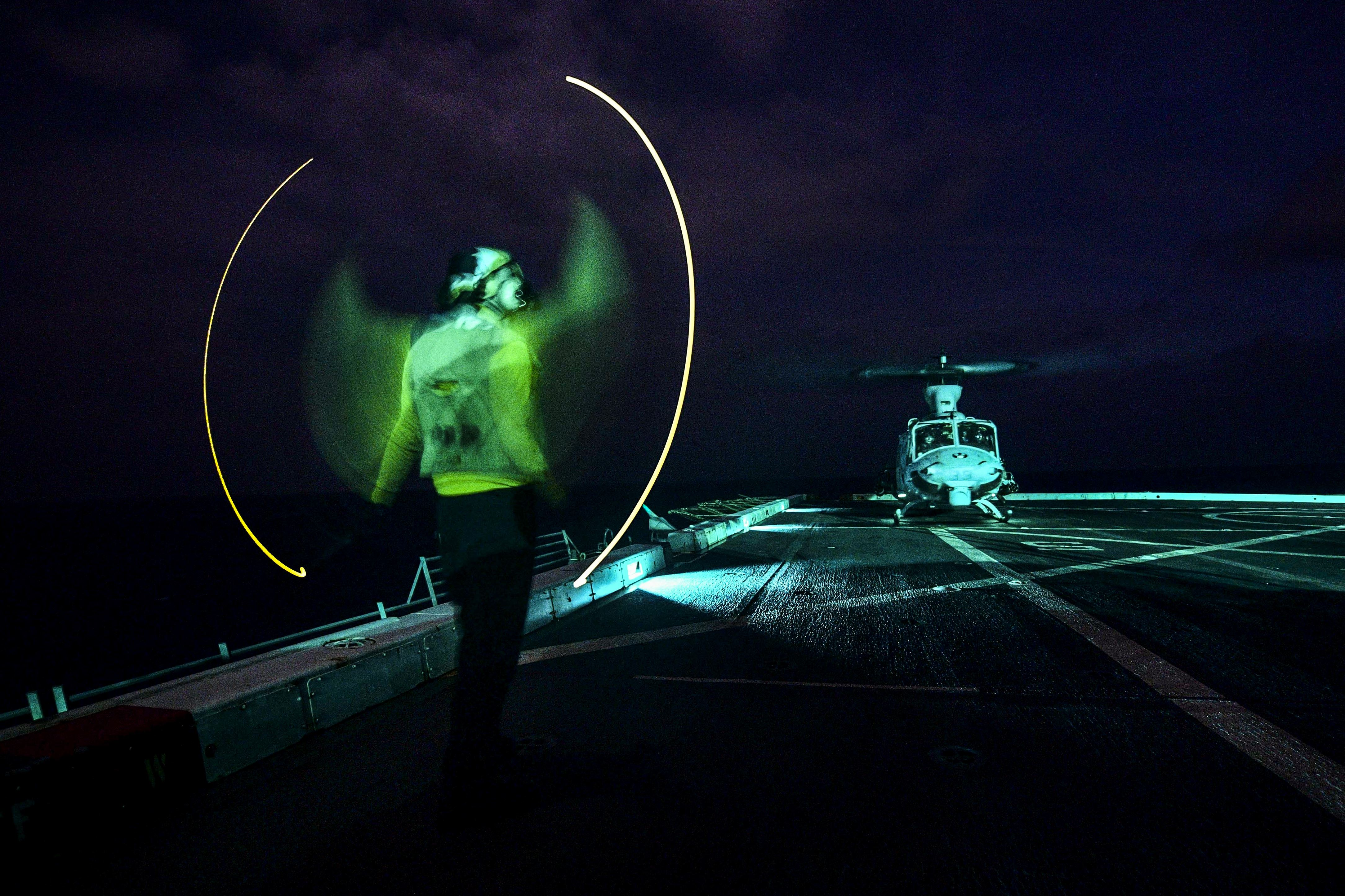 Navy Seaman Ryan Sharland directs a UH-1Y Venom helicopter on the flight deck of the USS San Diego in the Indian Ocean, Dec. 28, 2017. (Justin A. Schoenberger/Navy)