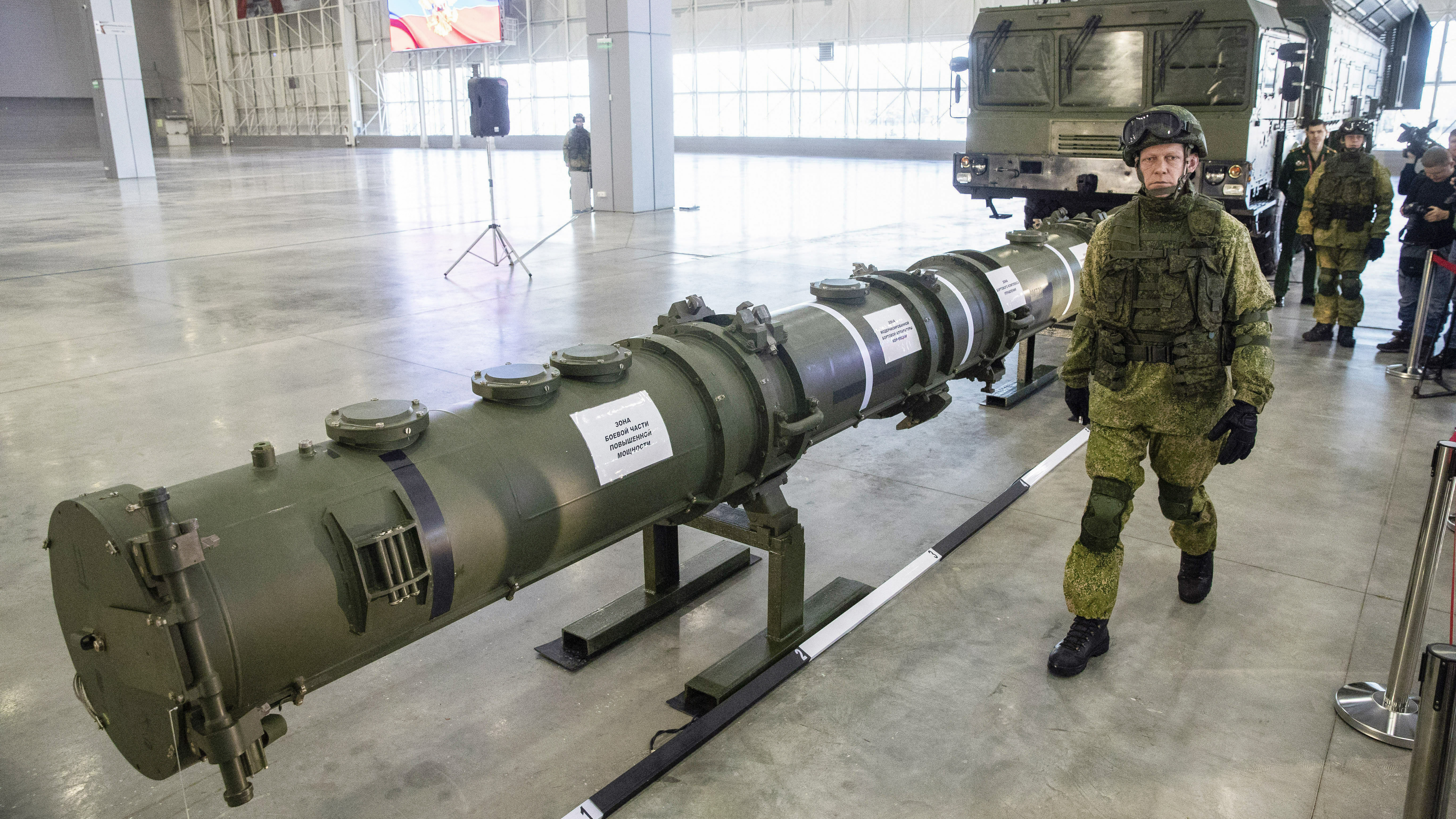 A Russian military officer walks past the 9M729 land-based cruise missile on display with its launcher, right, in Kubinka outside Moscow, Russia, Wednesday, Jan. 23, 2019. The Russian military on Wednesday rolled out its new missile and spelled out its specifications, seeking to dispel the U.S. claim that the weapon violates a key nuclear arms pact. (AP Photo/Pavel Golovkin)