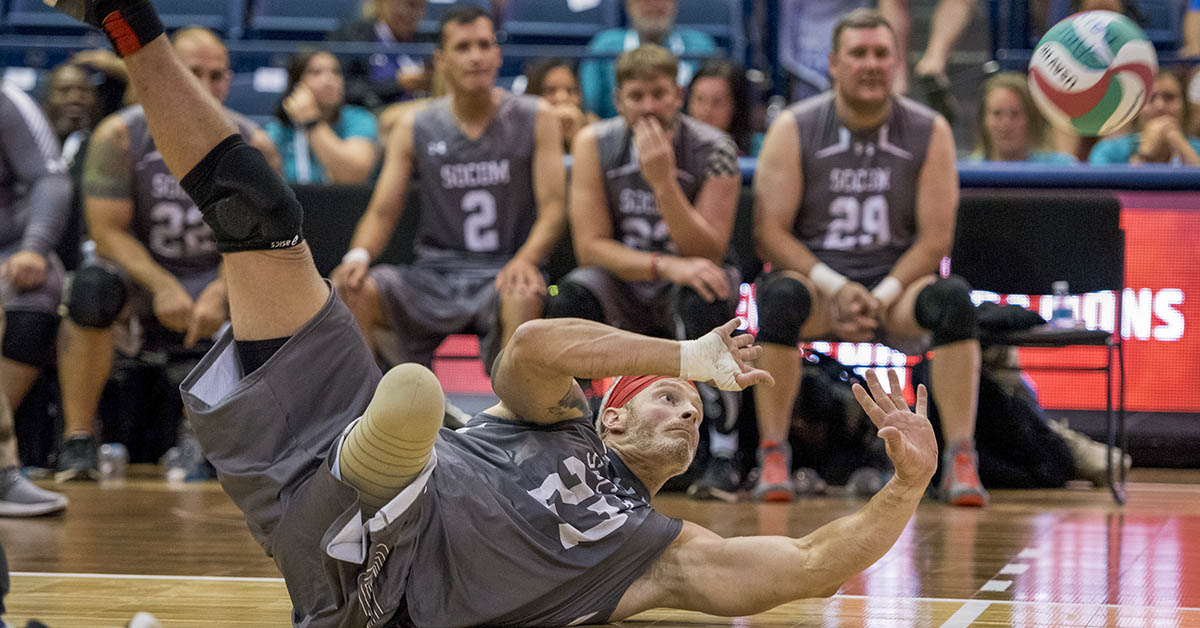 SOCOM Sgt. 1st Class Brant Ireland dives for a ball against Army in the bronze medal sitting volleyball match during the 2018 DoD Warrior Games at the U.S. Air Force Academy in Colorado Springs on June 8, 2018. Army defeated SOCOM to win the bronze medal. (Roger L. Wollenberg/DoD)