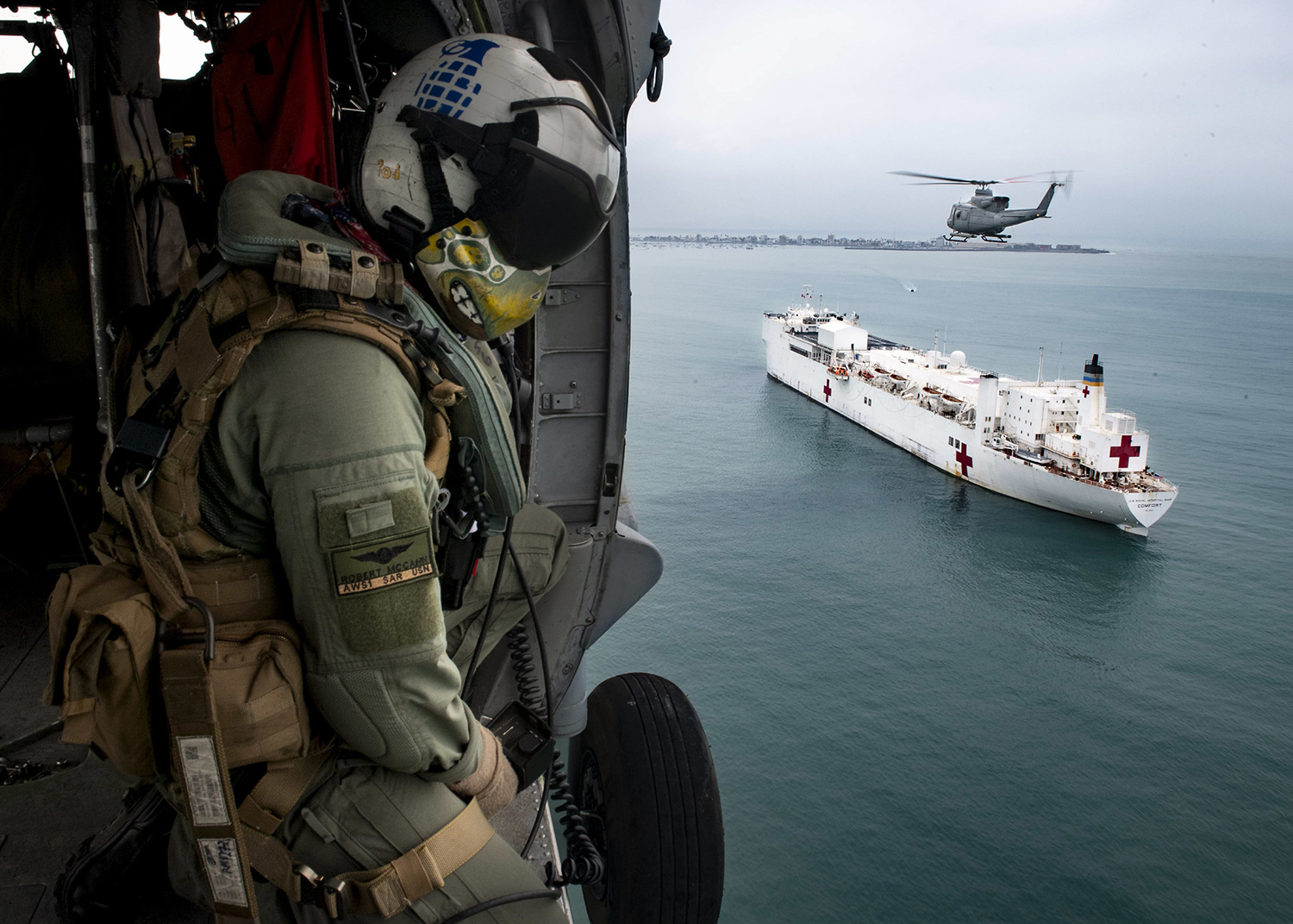 Naval Aircrewman (Helicopter) 1st Class Robert P. McCann flies in an MH-60S Sea Hawk helicopter alongside a Peruvian military Bell 412 on July 21, 2019, over the hospital ship USNS Comfort (T-AH 20). (Mass Communication Specialist 2nd Class Morgan K. Nall/Navy)