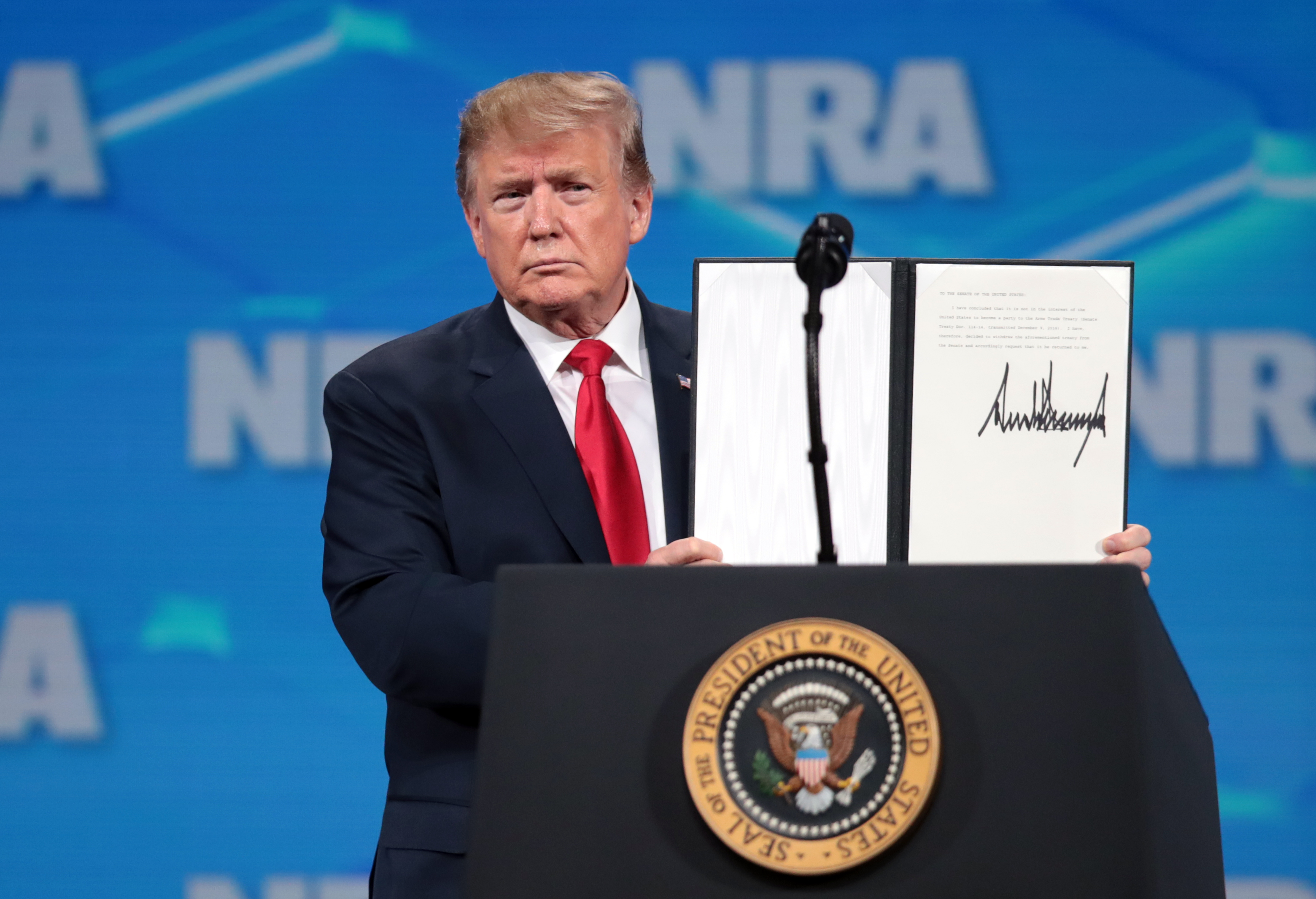 U.S. President Donald Trump shows off a signed document rejecting the U.N. Arms Trade Treaty at the annual meeting of the National Rifle Association on April 26, 2019, in Indianapolis, Ind. (Scott Olson/Getty Images)