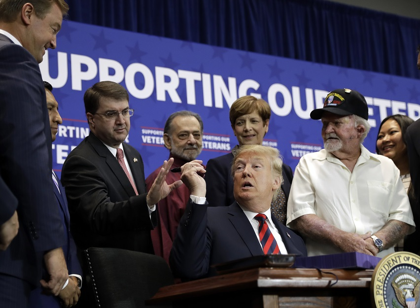 President Donald Trump hands a pen to Veterans Affairs Secretary Robert Wilkie during a spending bill signing ceremony at VA Southern Nevada Healthcare System on Sept. 21, 2018, in Las Vegas. (Evan Vucci/AP)