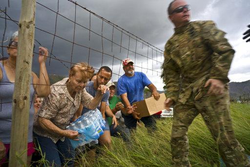 A member of the Puerto Rico National Guard delivers food and water to victims of Hurricane Maria, in Morovis, Puerto Rico. (Ramon Espinosa/AP)
