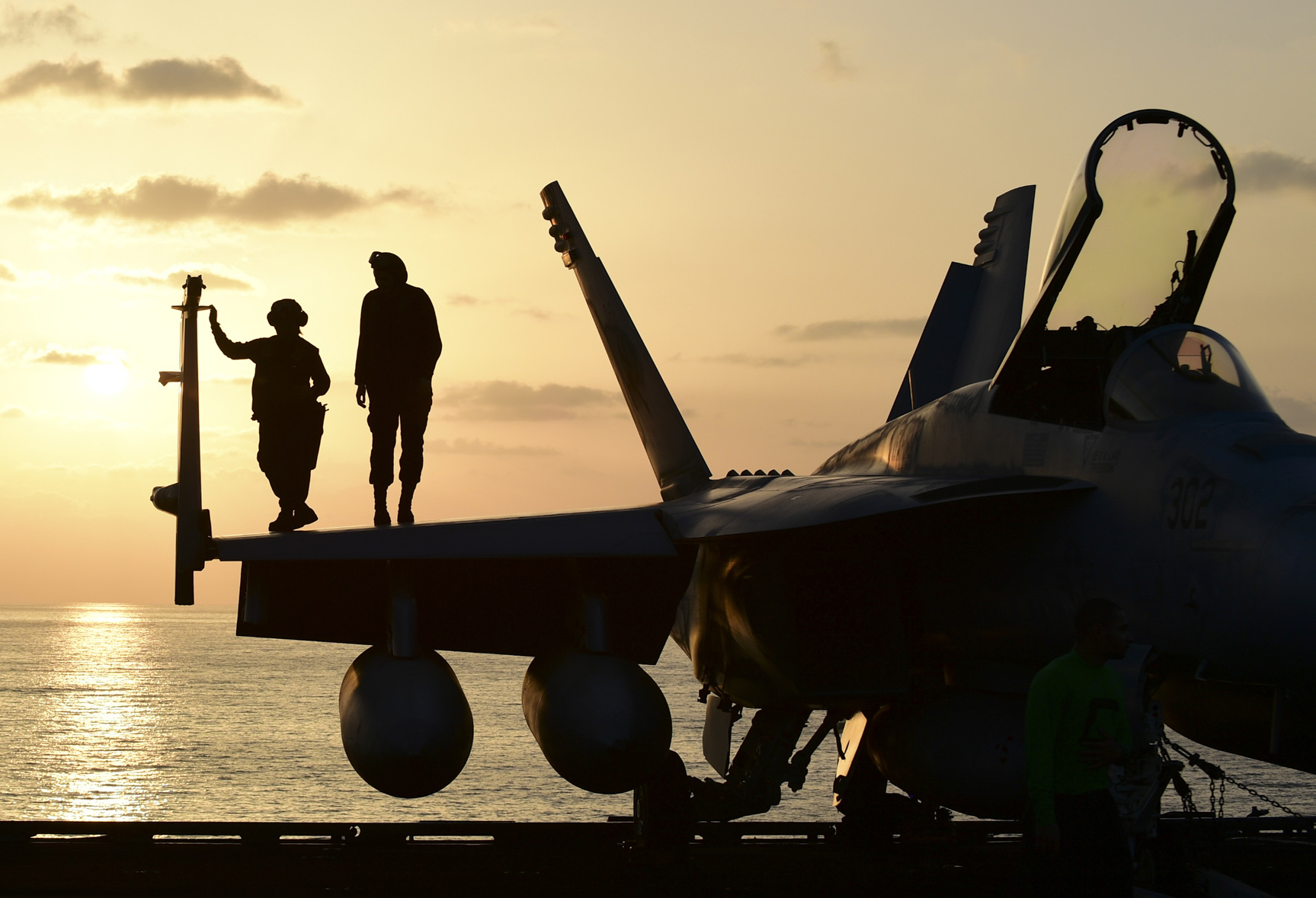 Sailors watch the sunset on the wing of an F/A-18E Super Hornet assigned to the
