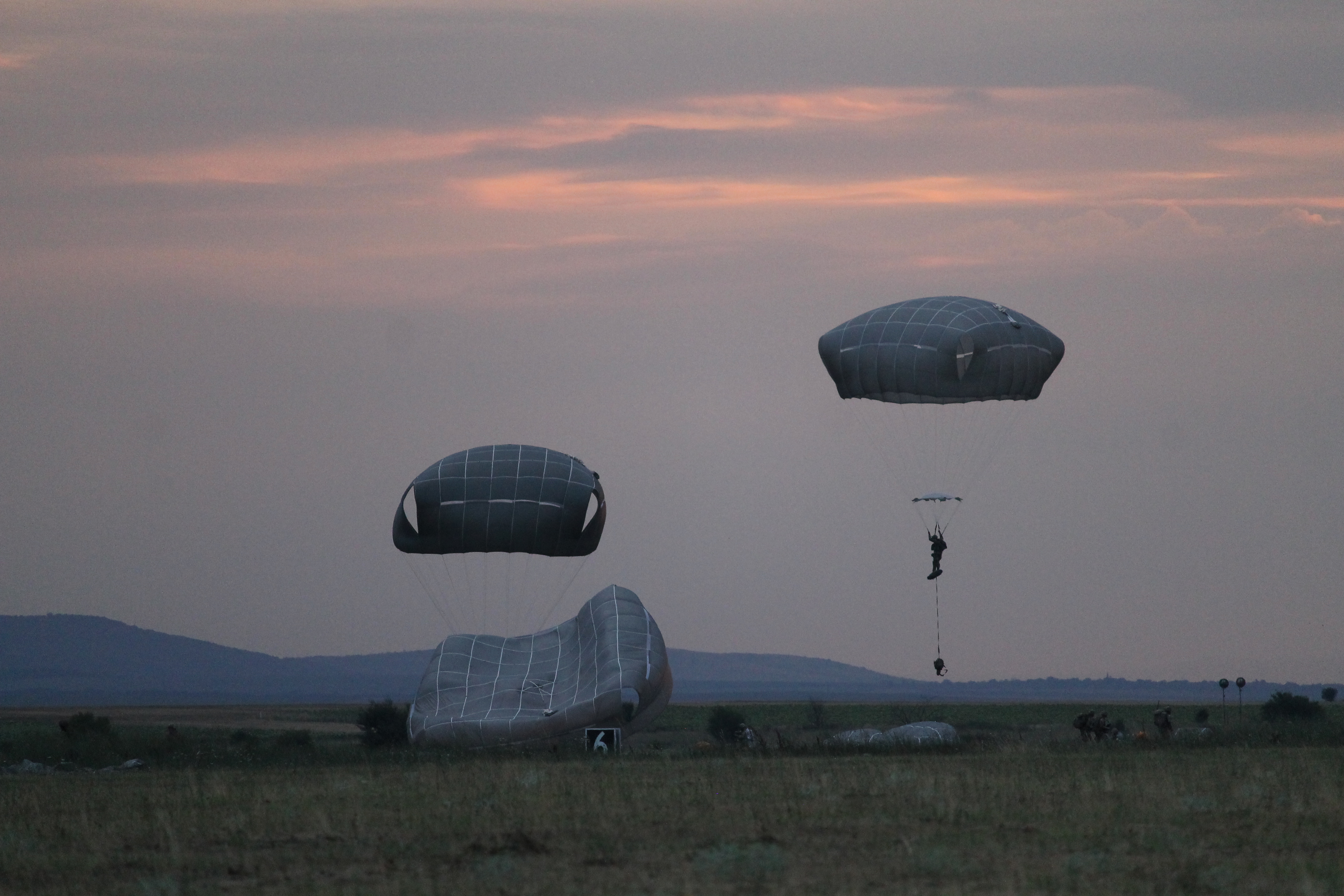 Paratroopers from the 173rd continue to land in the drop zone as night falls. (Jen Judson/Staff)