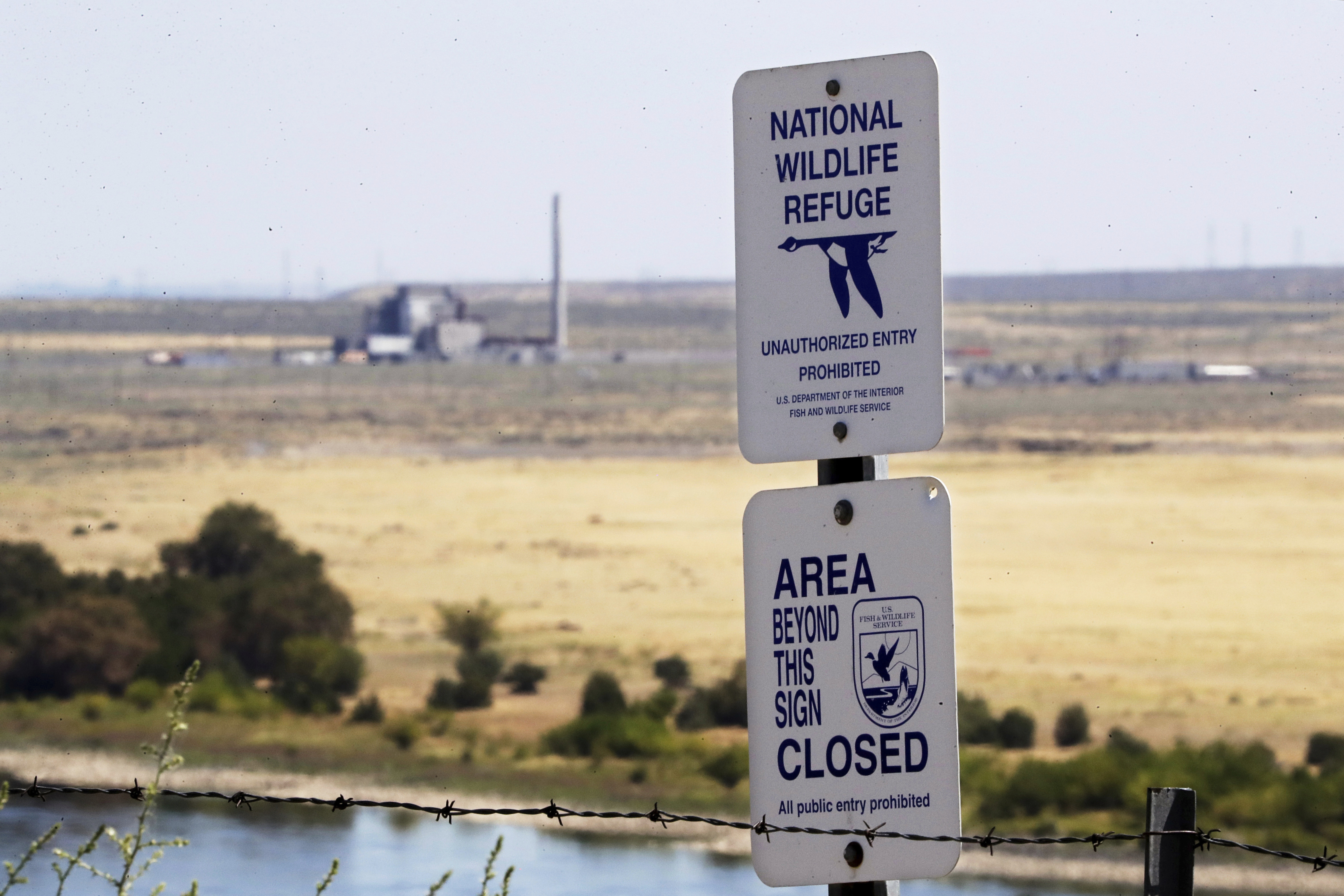 In this Aug. 14, 2019, photo, a sign designates a boundary of the Hanford Reach National Monument as the world's first large scale nuclear reactor, the B Reactor, is seen in the background where it sits unused on the Hanford Nuclear Reservation along the Columbia River near Richland, Wash. (Elaine Thompson/AP)