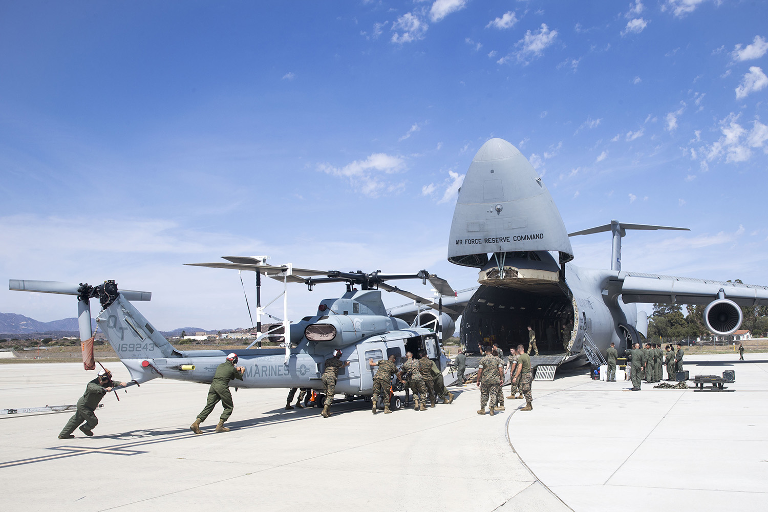 Marines and airmen assist in loading a UH-1Y Venom into C-5M Super Galaxy at Marine Corps Air Station Camp Pendleton, Calif., Sept. 16, 2019. (Lance Cpl. Drake Nickels/Marine Corps)