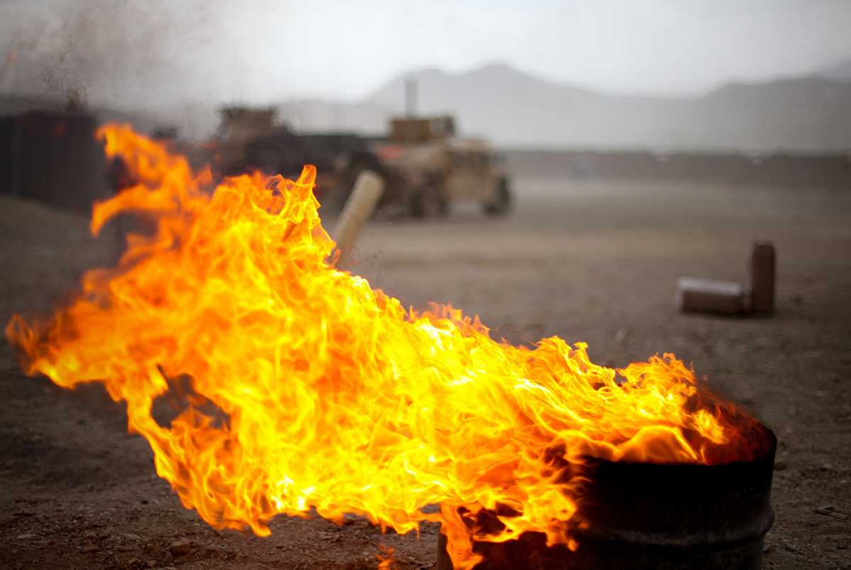 The flames of a burn pit picks up with the winds as a storm approaches Combat Outpost Tangi in the Tangi Valley, Afghanistan, Aug. 31, 2009. (Staff Sgt. Teddy Wade/Combat Camera)