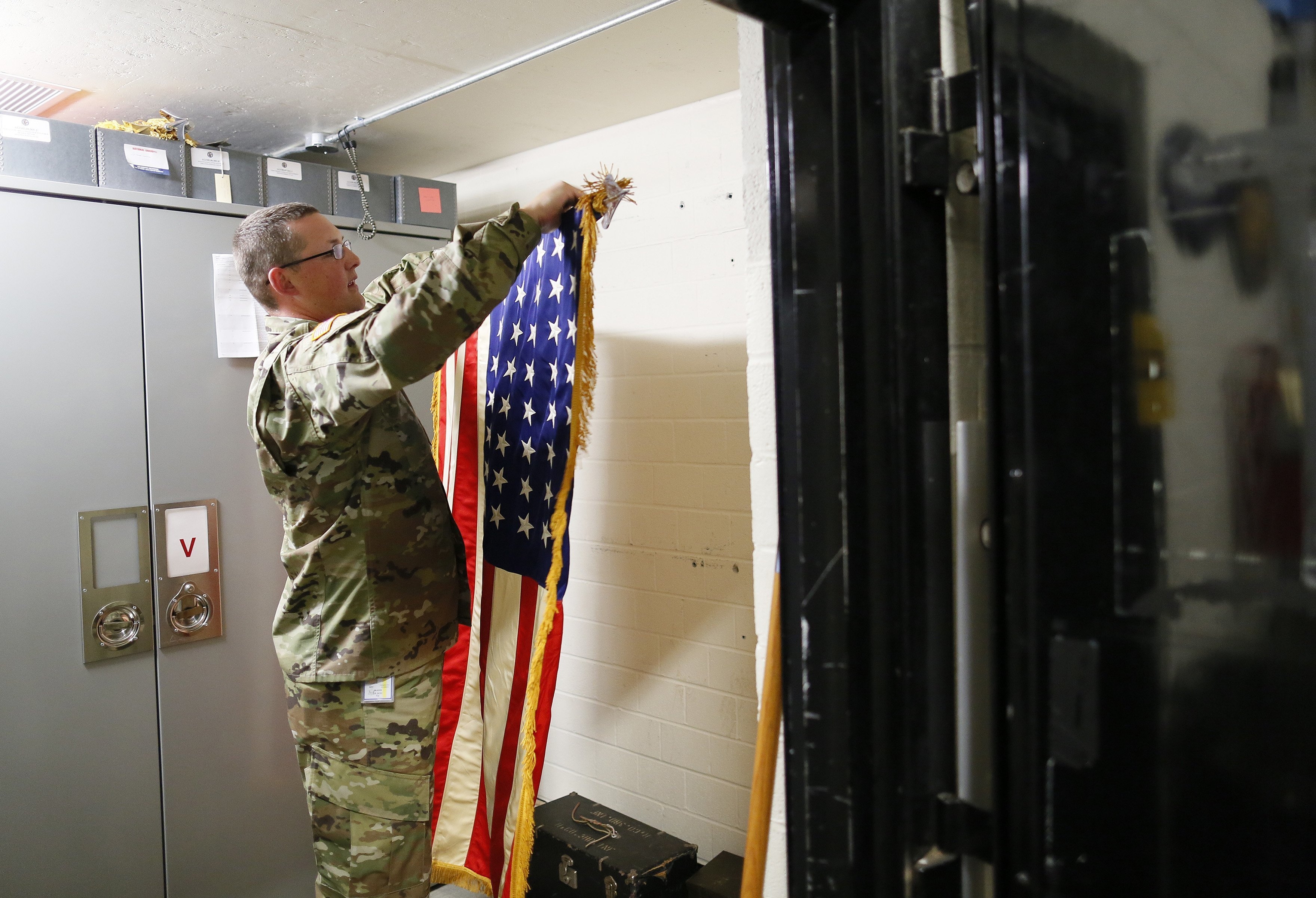 In this July 17, 2018, photo, Sgt. 1st Class Josh Mann, the Ohio Army National Guard historian, rolls an American flag that had been hanging in the temperature and humidity-controlled vault inside the Beightler Armory in Columbus, Ohio. The Ohio National Guard is celebrating its 230 years of service. (Adam Cairns/The Columbus Dispatch via AP)