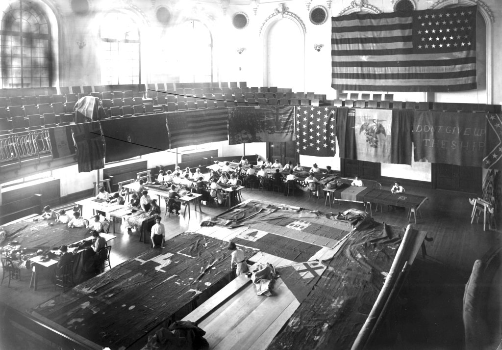 This 1913 photo made available by the United States Naval Academy Museum shows the auditorium of Mahan Hall at the U.S. Naval Academy in Annapolis, Md. Dozens of women in the museum's Mahan Hall, used a patented stitching pattern to help preserve fabric. (U.S. Naval Academy Museum via AP)