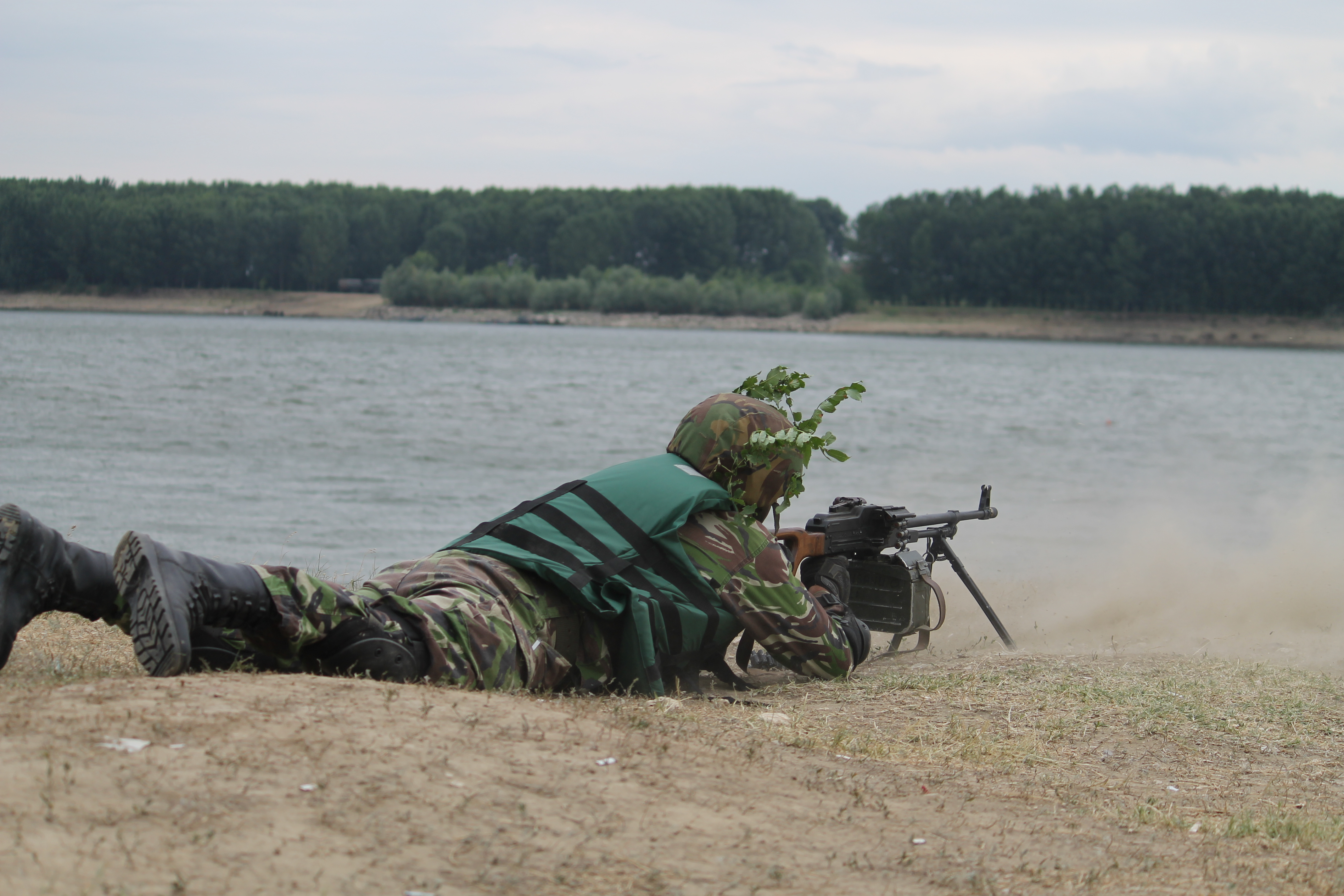 A soldier fires, providing cover for troops attempting to cross the Danube with a high-speed boat. (Jen Judson/Staff)