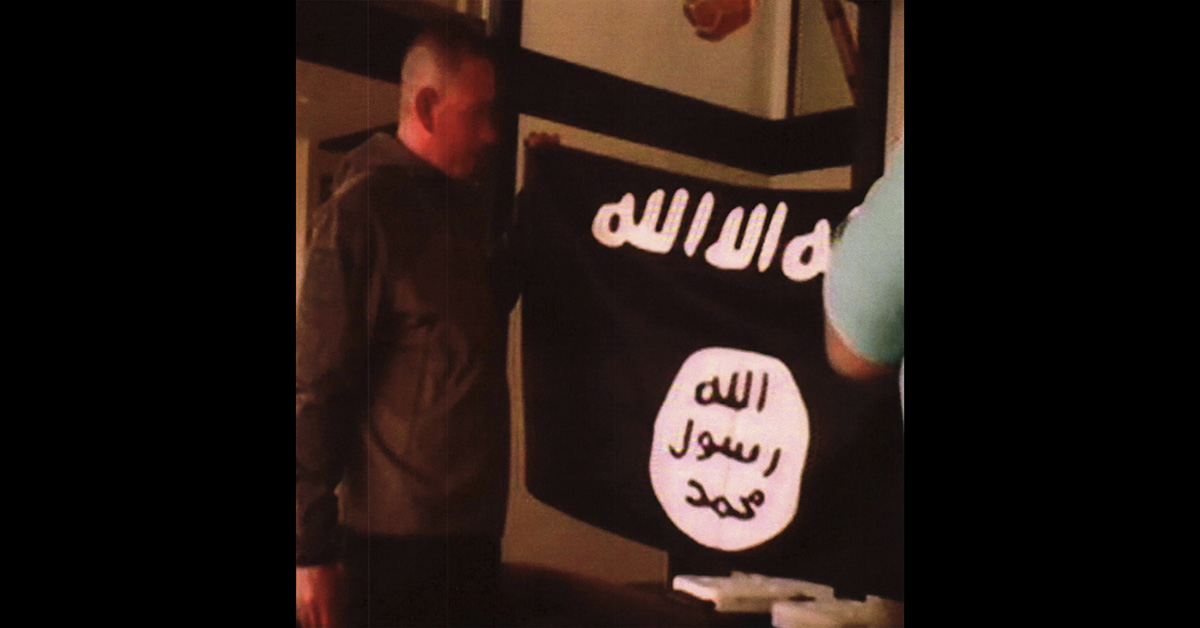 In this image taken from FBI video and provided by the U.S. Attorney's Office in Hawaii on July 13, 2017, Army Sgt. 1st Class Ikaika Kang holds an Islamic State group flag after allegedly pledging allegiance to the group at a house in Honolulu on July 8. (FBI/U.S Attorney's Office, District of Hawaii via AP)