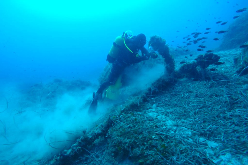 A diver searches the seabed near the island of Fourni. Greece's culture ministry says a Greek-U.S. team has located traces of five more ancient shipwrecks in the eastern Aegean Sea, raising to 58 the number of wrecks located since 2015 around Fourni, a notoriously dangerous point on the ancient shipping route. (Greek Culture Ministry via AP)