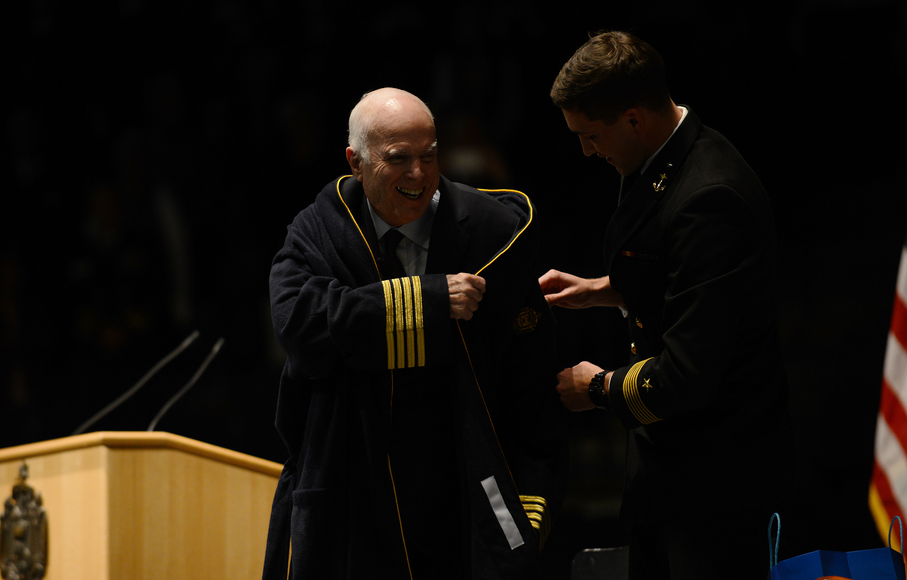 Sen. John McCain, R-Ariz., chairman of the Senate Armed Services Committee, laughs while trying to put on his gift, a Navy bathrobe, after addressing the Naval Academy on Oct. 30, 2017, in Annapolis, Md. He spoke about the importance of American leadership and service to one's country. (Astrid Riecken/Getty Images)