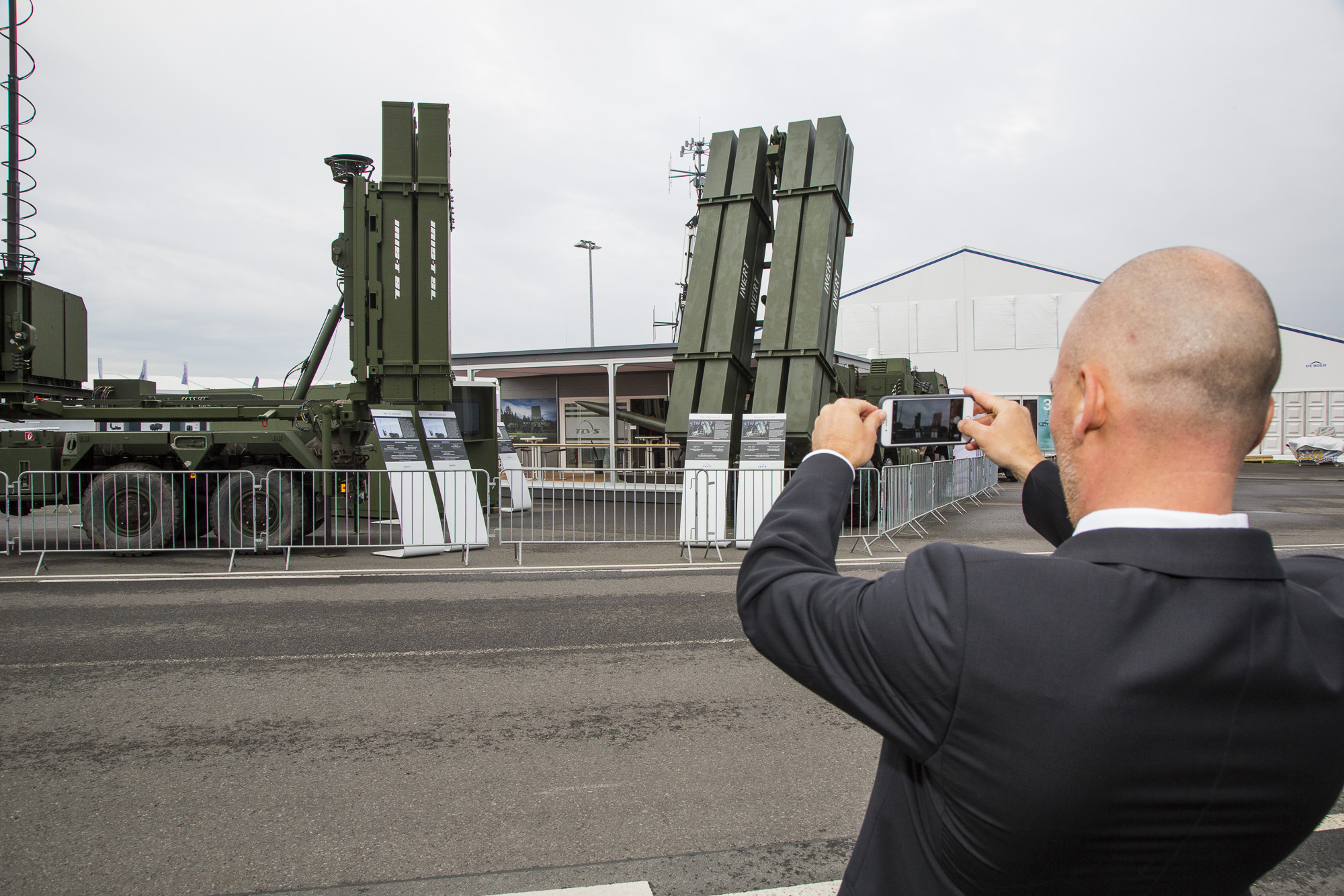A visitor of the 2018 Berlin Air Show takes a photo of TLVS hardware displayed on the tarmac at Schoenefeld Airport in April 2018. (Lockheed Martin)