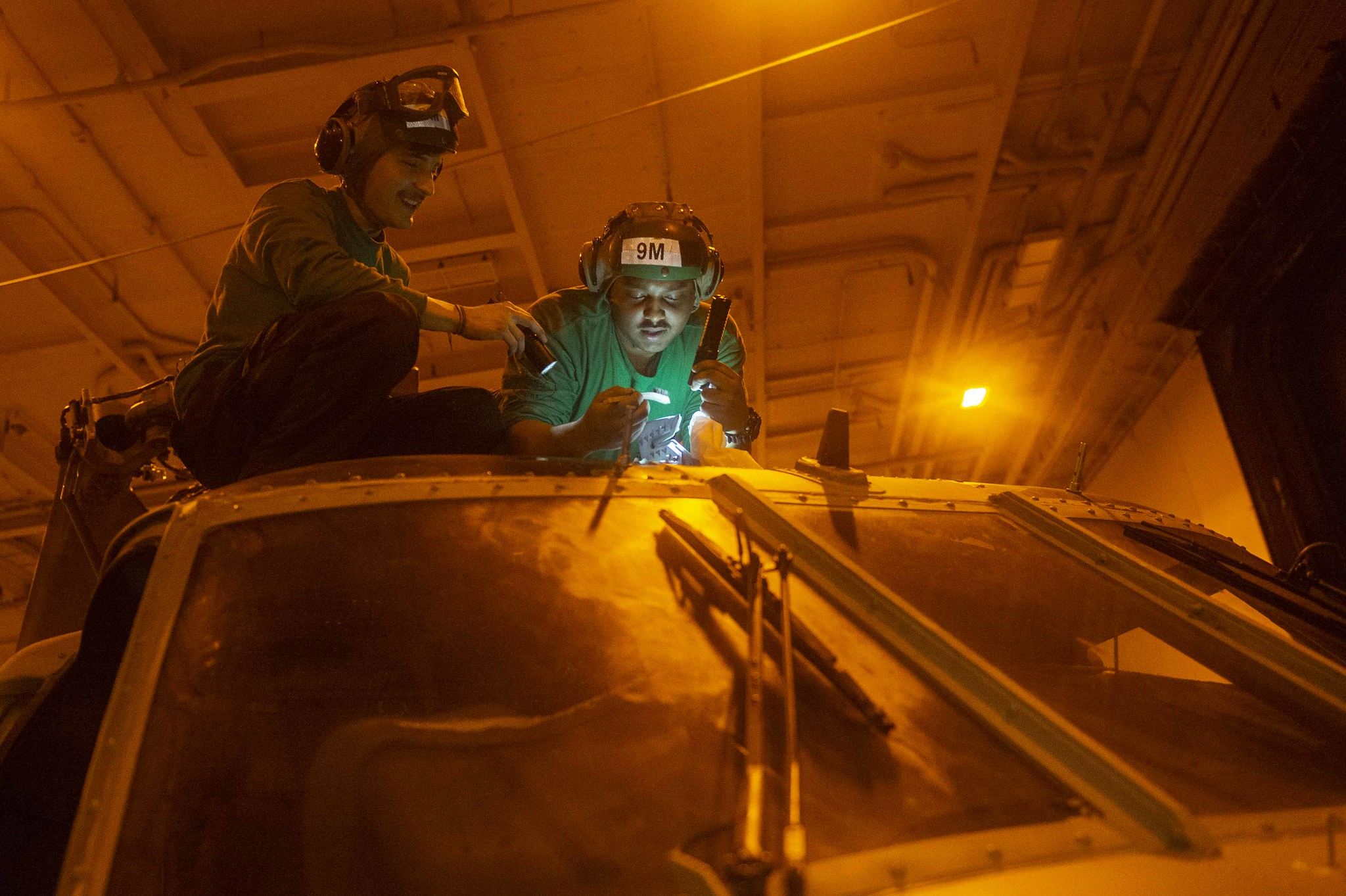 Aviation Structural Mechanic 2nd Class Daniel Rivera and Aviation Structural Mechanic 3rd Class Anthony Morales remove corrosion on the main rotor head of an MH-60S Seahawk helicopter in the hangar bay of the aircraft carrier USS Harry S. Truman (CVN 75) on Jan. 2, 2020, in the Arabian Sea, Jan. 2, 2020. (Mass Communication Specialist 3rd Class Megan Wollam/Navy)