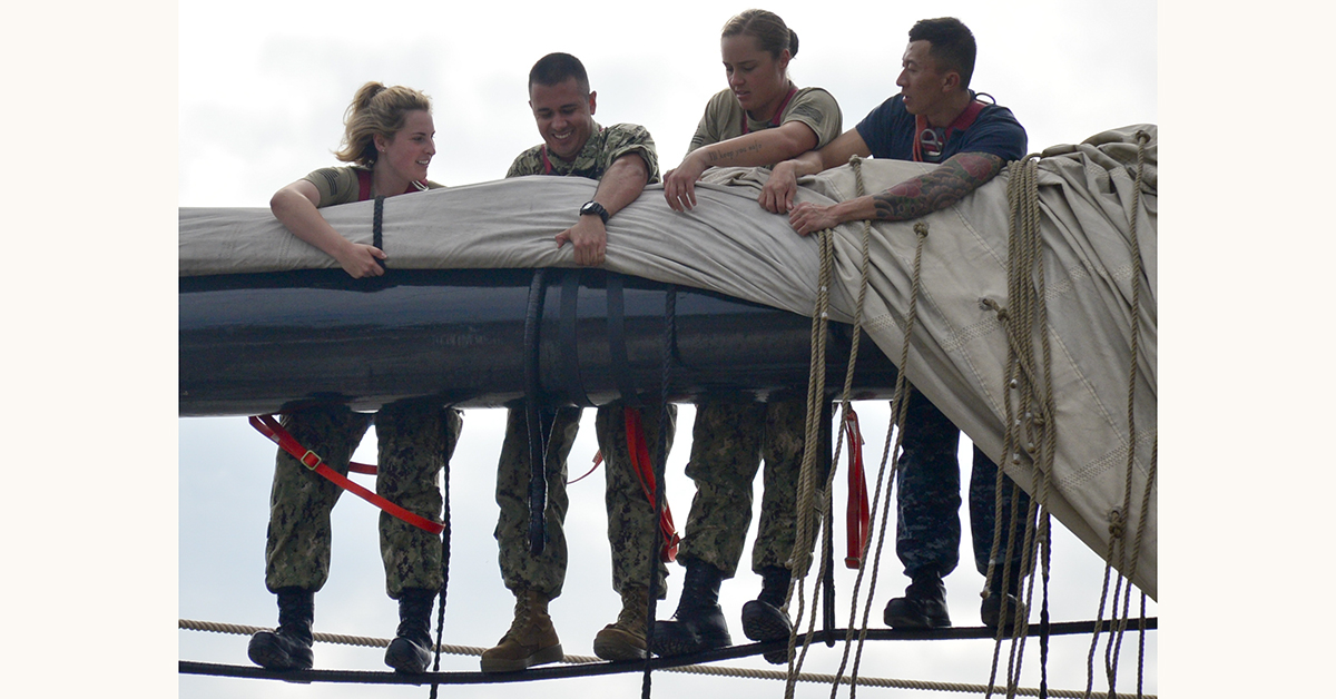 Seaman Emma Hoernline, far left, and Seaman Ashley Watson, middle right, assigned to USS Constitution, assist chief petty officer selectees Construction Mechanic 1st Class Mario PadillaCruz, middle left, and Electrician's Mate 1st Class Tho Nguyen, far right, while furling USS Constitution's main topsail during Chief Petty Officer (CPO) Heritage Week. CPO Heritage Week is a week dedicated to mentoring the Navy's newest chiefs through naval history and heritage training aboard America's Ship of State, USS Constitution. (MC3 Casey Scoular/Navy)